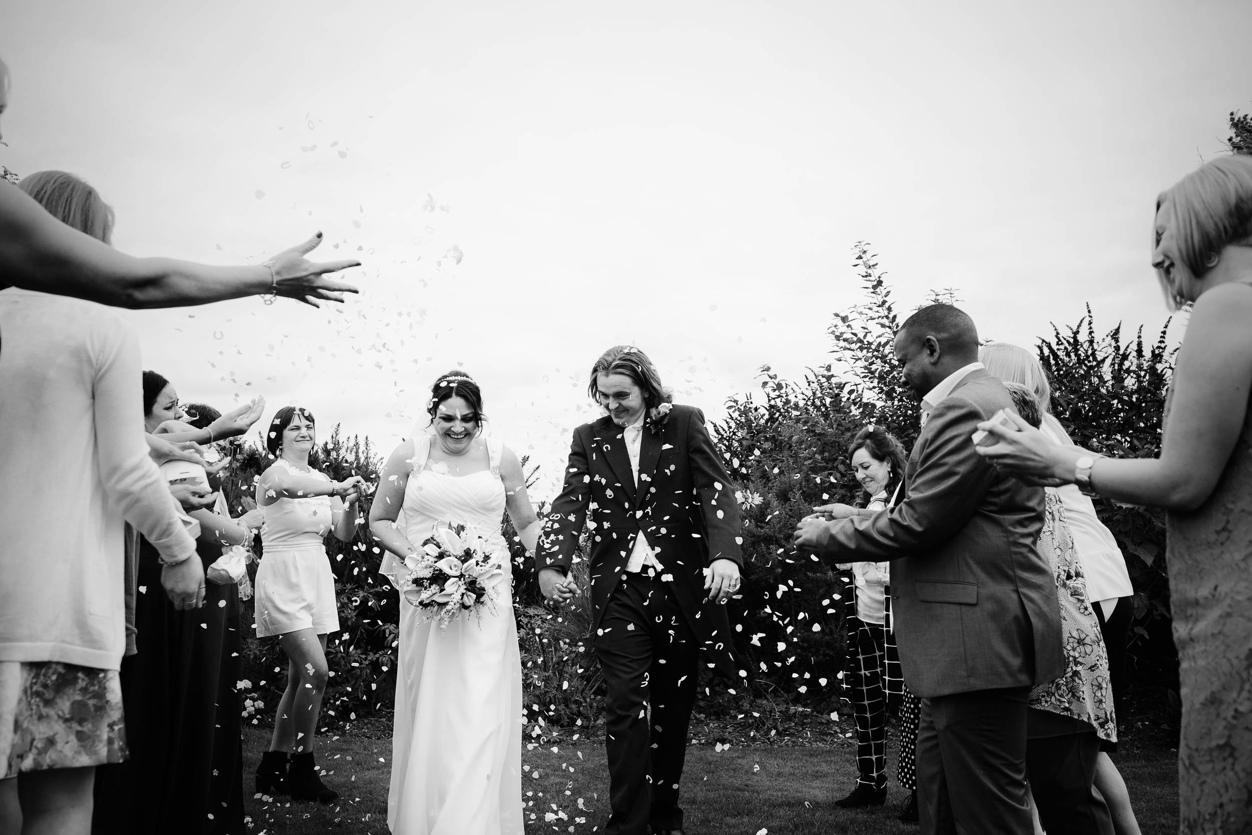 The bride and groom are showered with confetti at their wedding at South Causey Inn, Durham, in this black and white photograph