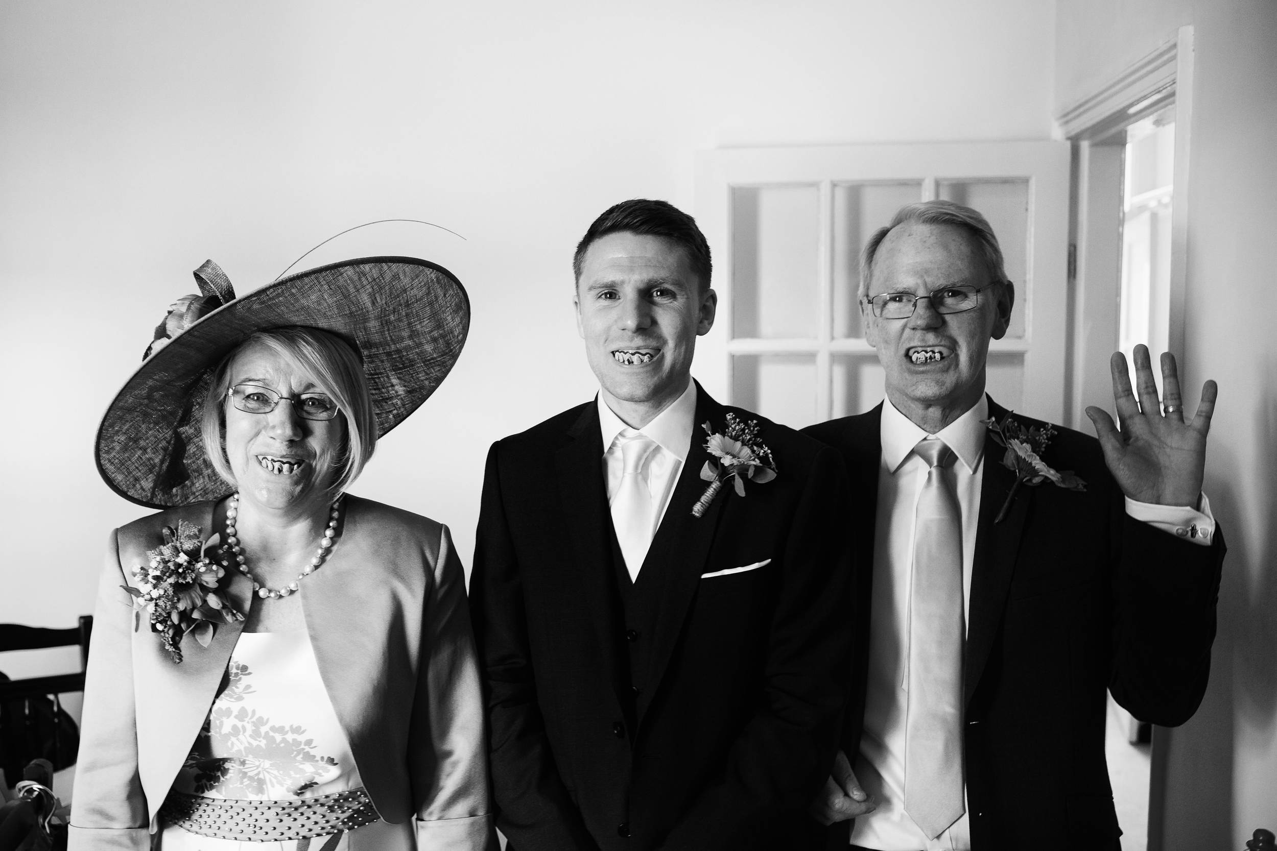 An amusing black and white photograph of the groom and parents of the groom wearing false teeth at home in Sunderland