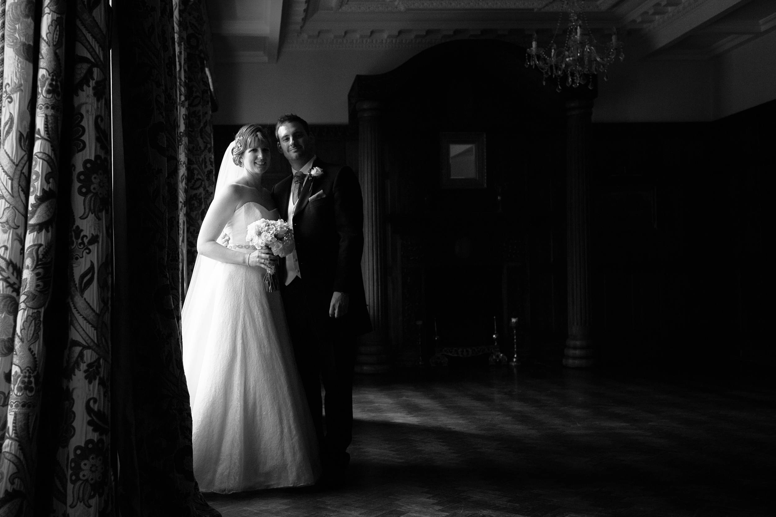 The bride and groom lit by window light at Ellingham Hall, Northumberland in this moody black and white photograph