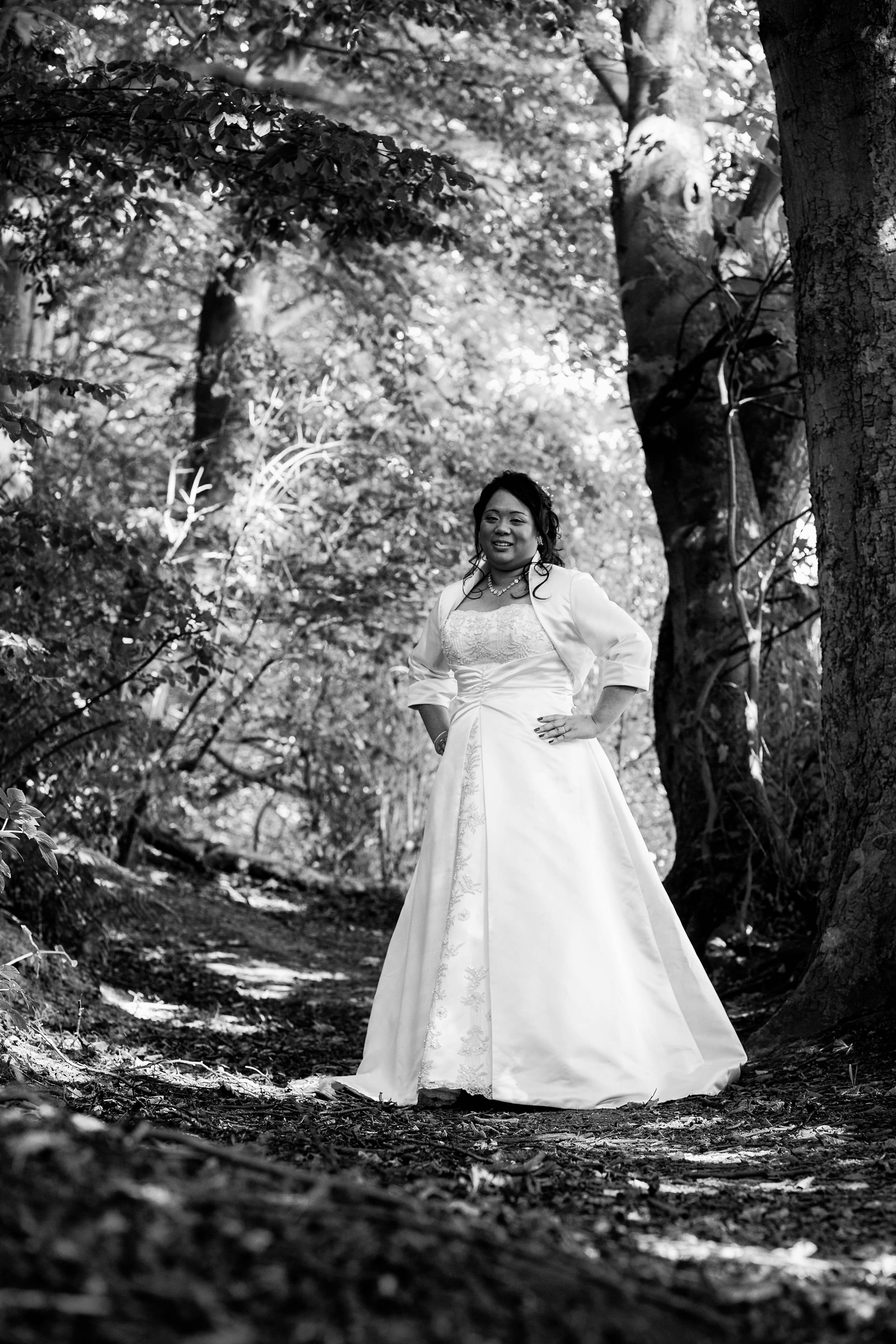 A black and white portrait of the bride deep in the sun drenched woods at an outdoor wedding in Durham