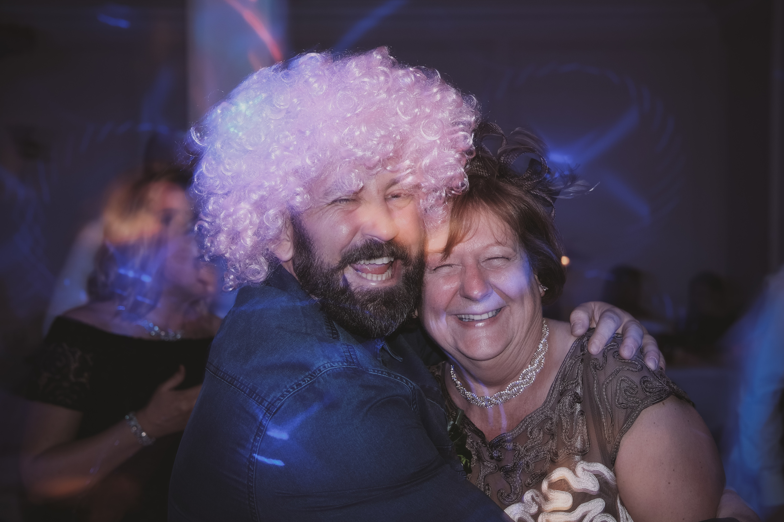 Newcastle Wedding Photographer // Guests cuddle on dance floor while wearing wig
