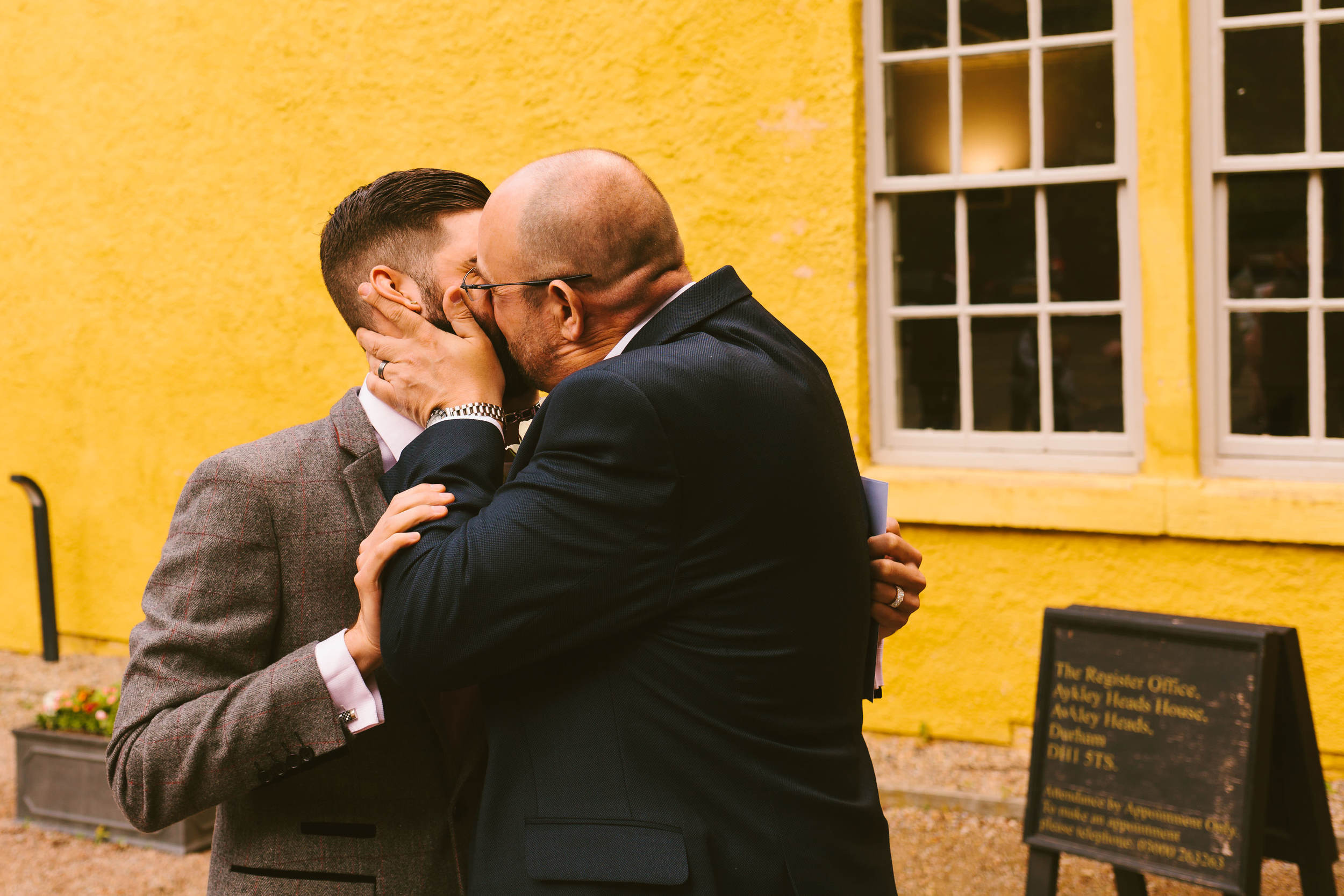 The father of the bride kisses the groom at a wedding in Durham