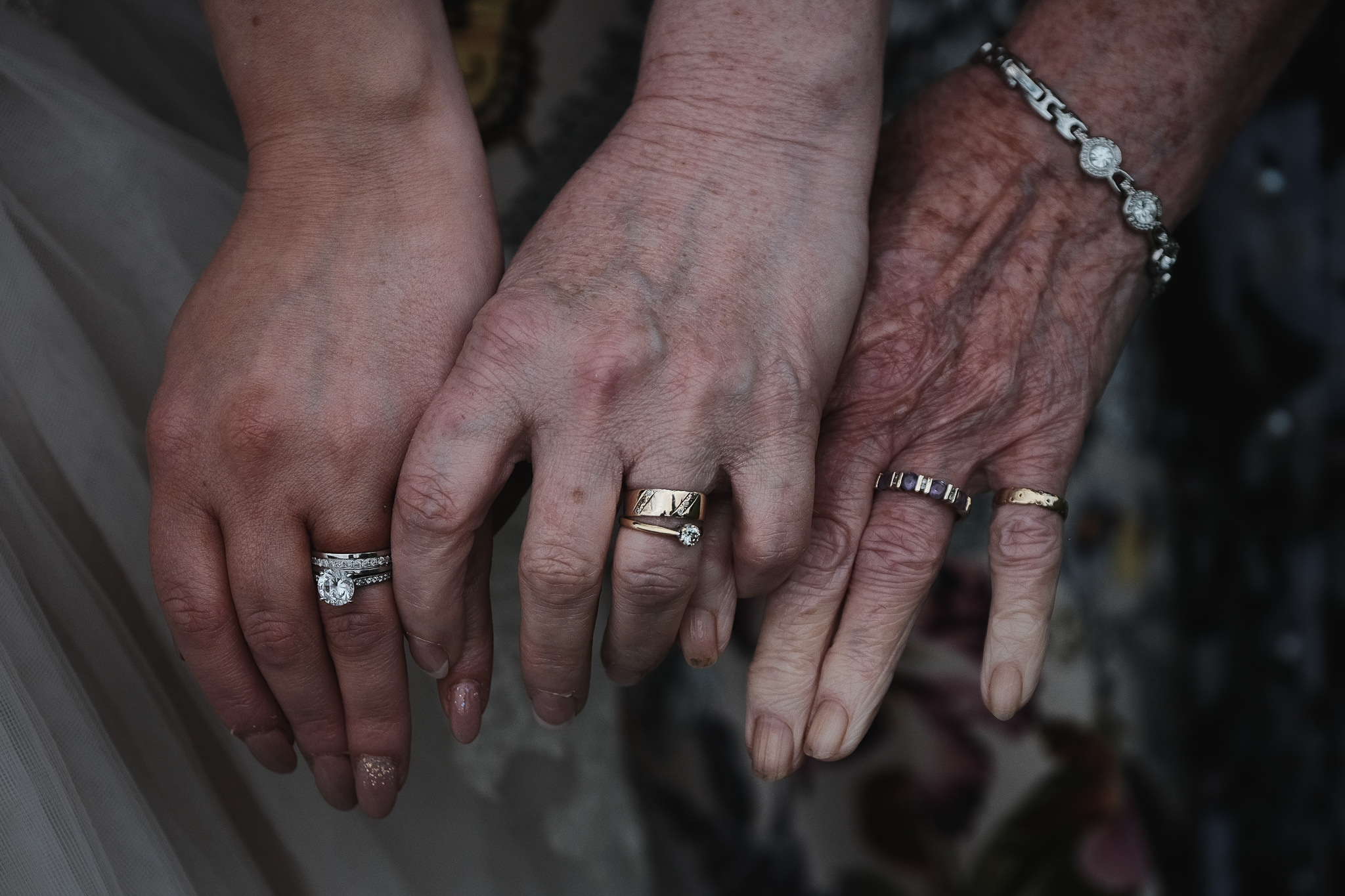 Bride mother and grandmother hold hands at Newton Hall Wedding in Northumberland photographed by Barry Forshaw