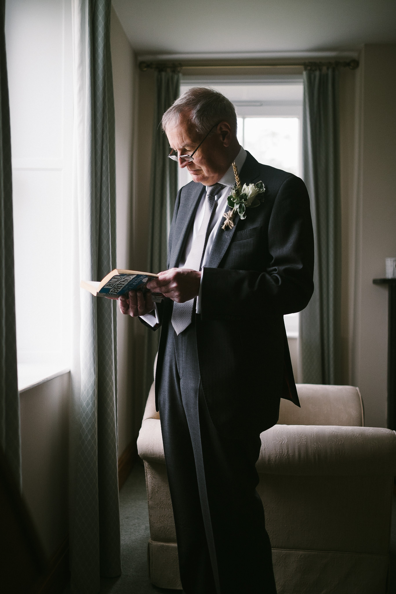 The father of the groom reads a book in front of a window before the wedding in Yorkshire by Barry Forshaw