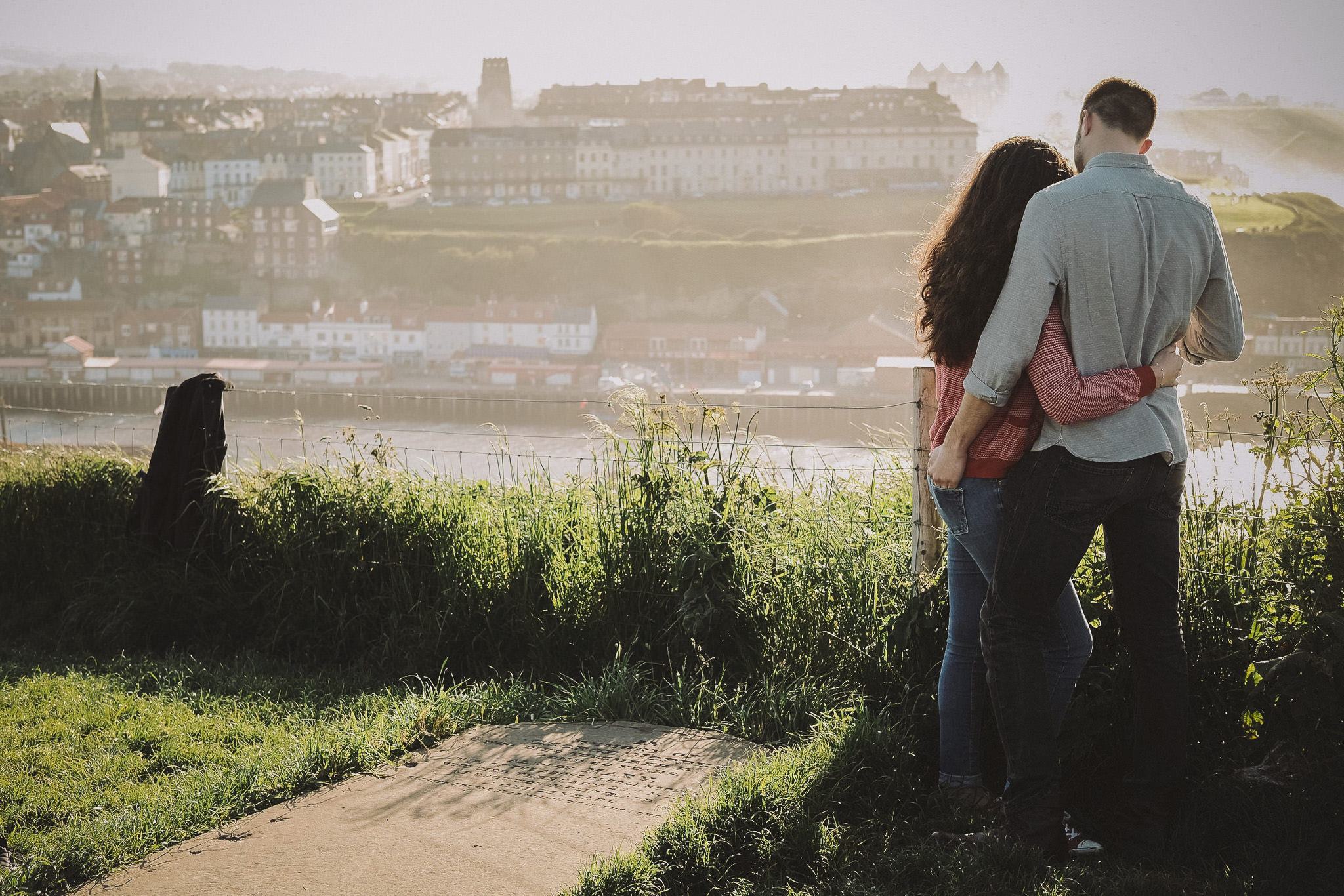 Katy and Tom cuddle while looking out over Whitby Habour in Yorkshire on a pre-wedding engagement shoot by Barry Forshaw