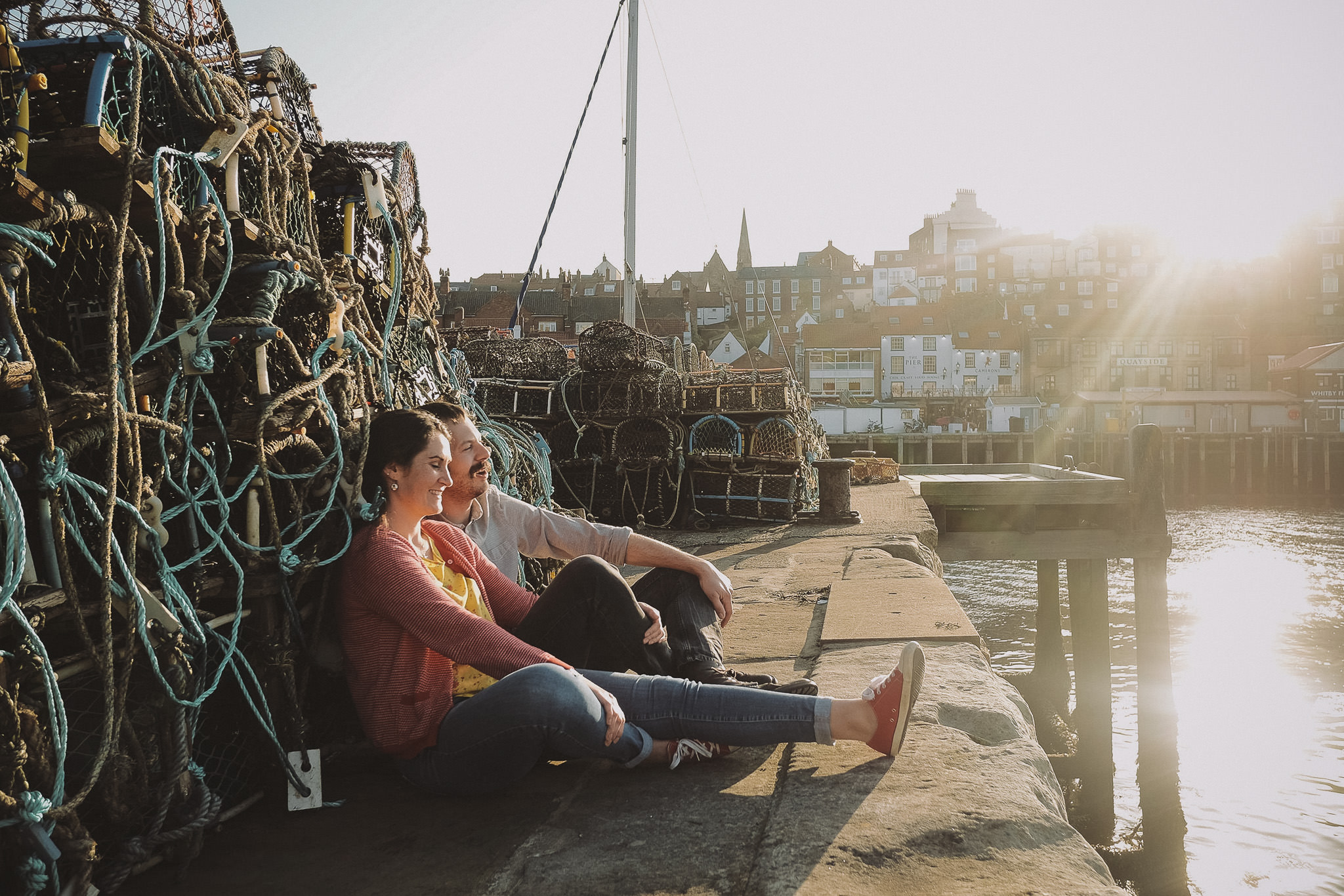 Katy and Tom sit amongst the fishing nets at Whitby Habour with the sun shining down in Yorkshire on a pre-wedding engagement shoot by Barry Forshaw
