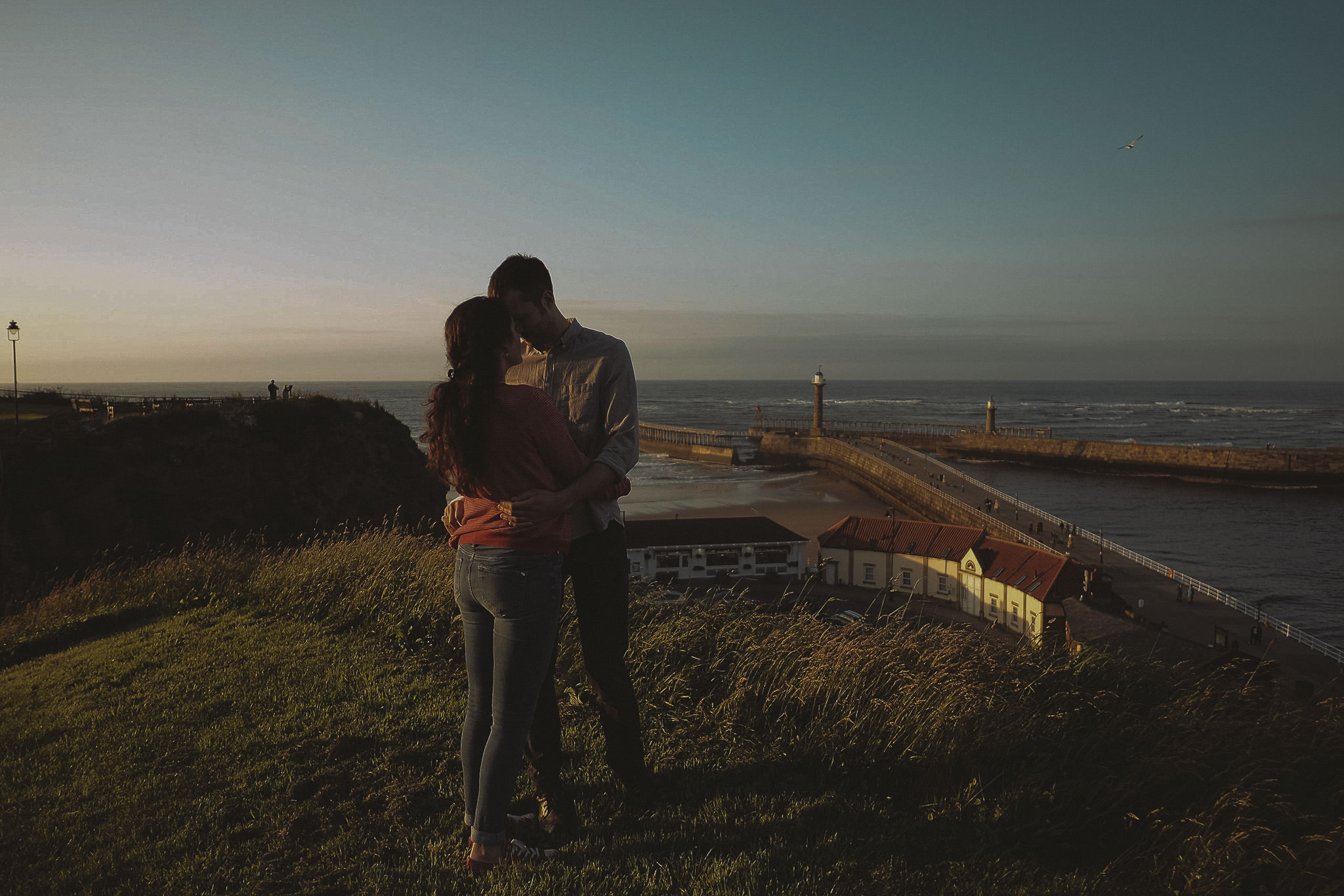 A silhouette of Katy and Tom hug as the sun goes down on a grassy hill on the Khyber Pass overlooking Whitby Habour in Yorkshire on a pre-wedding engagement shoot by Barry Forshaw