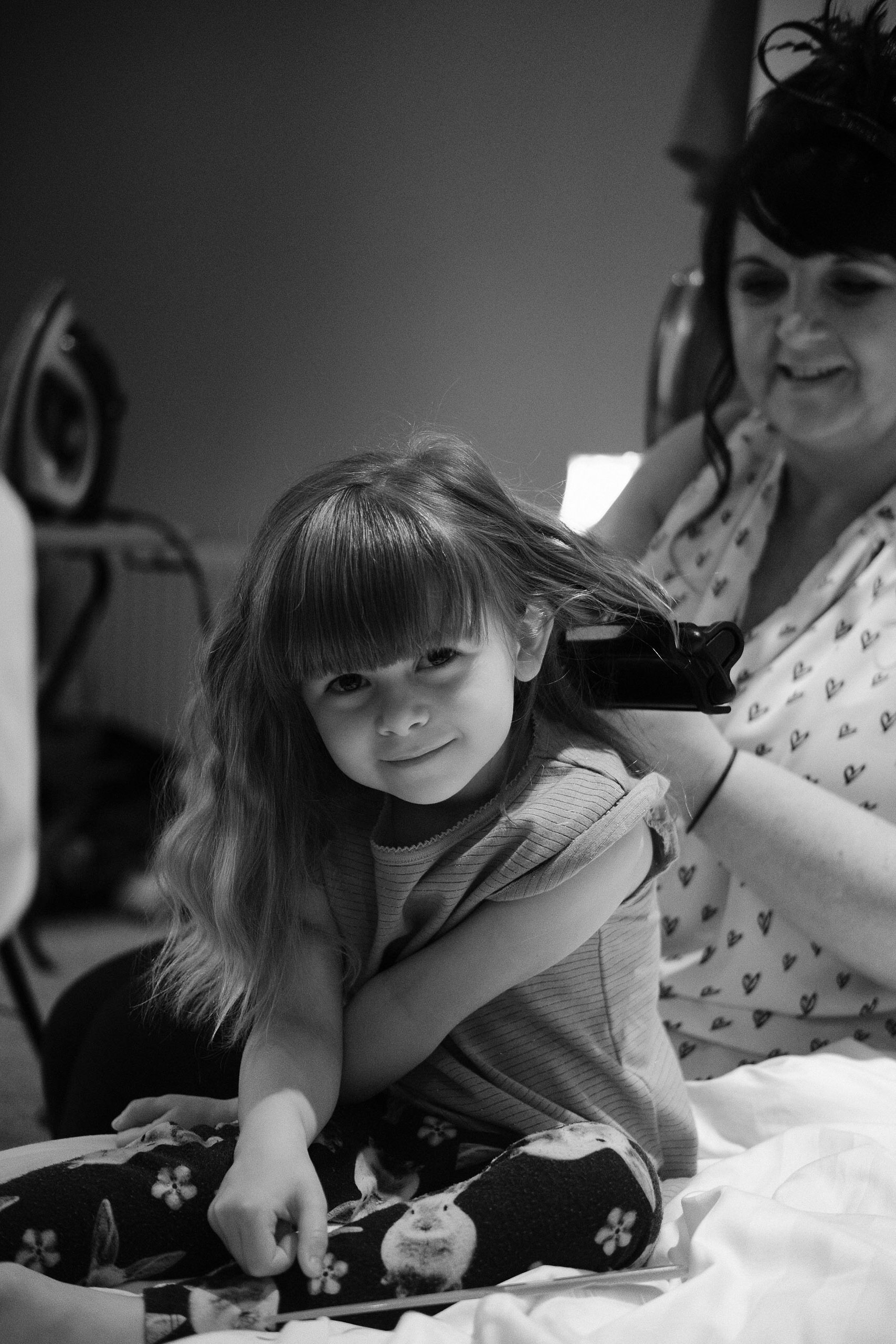 A black and white portrait of a flower girl having her hair styled at Newton Hall, Northumberland by Barry Forshaw