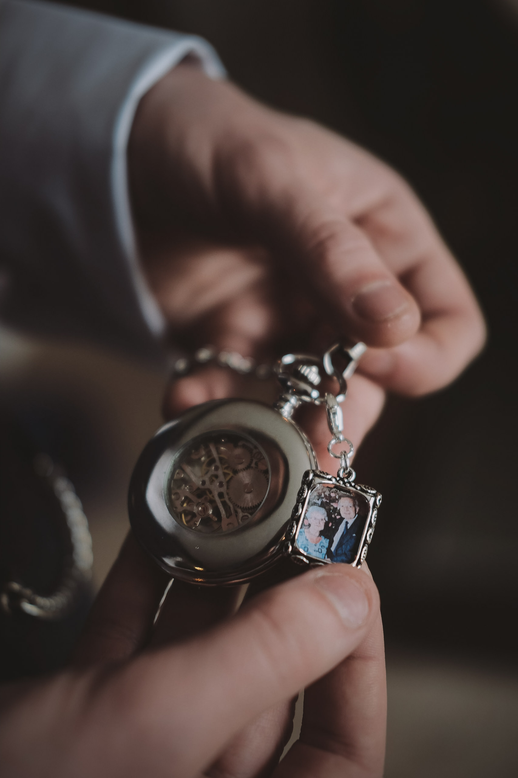 The groom shows off his pocket watch containing a photograph of his grandparents at Newton Hall, Northumberland by Barry Forshaw