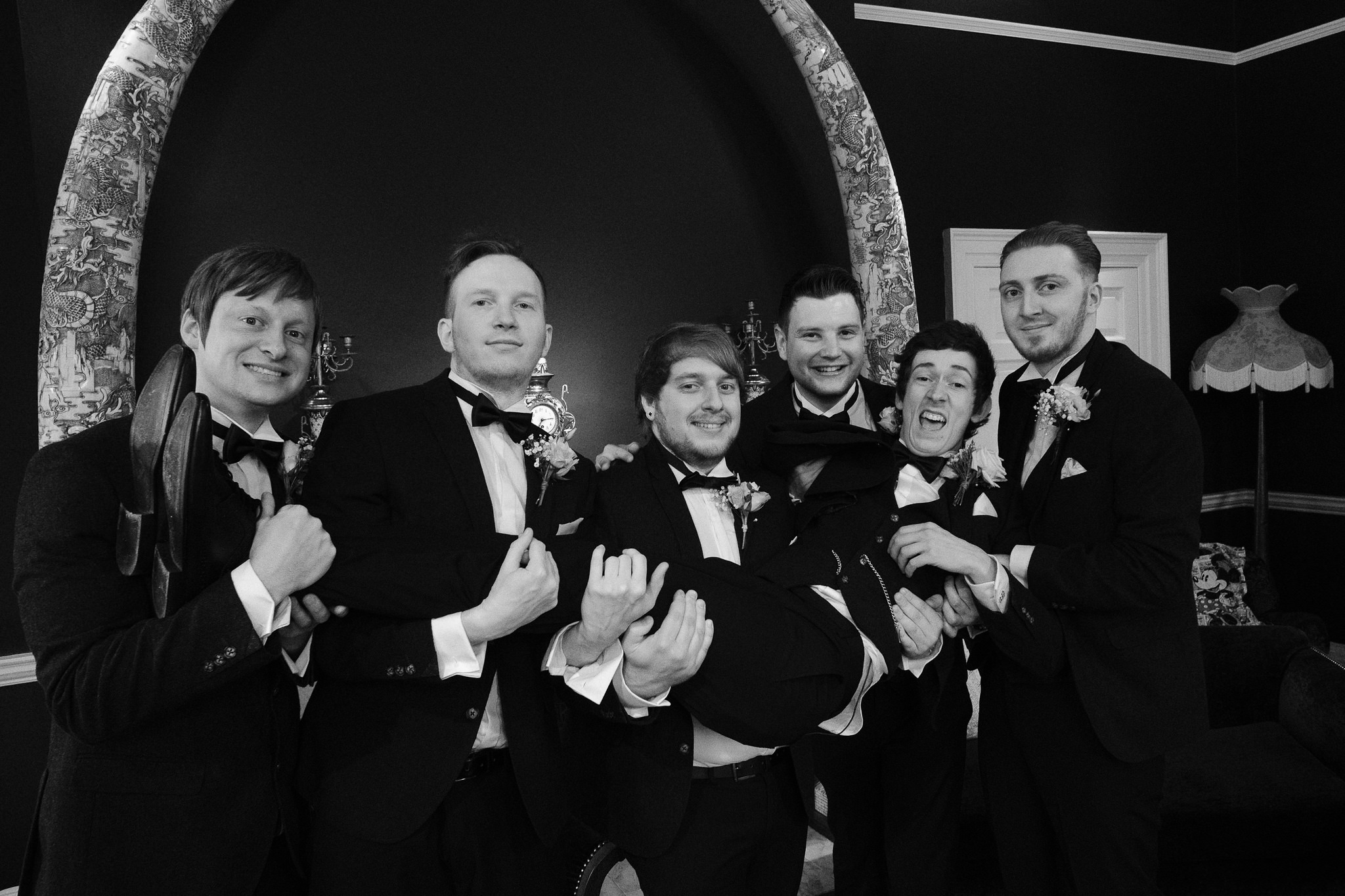 A black and white photo of the groomsmen holding the groom at Newton Hall, Northumberland by Barry Forshaw
