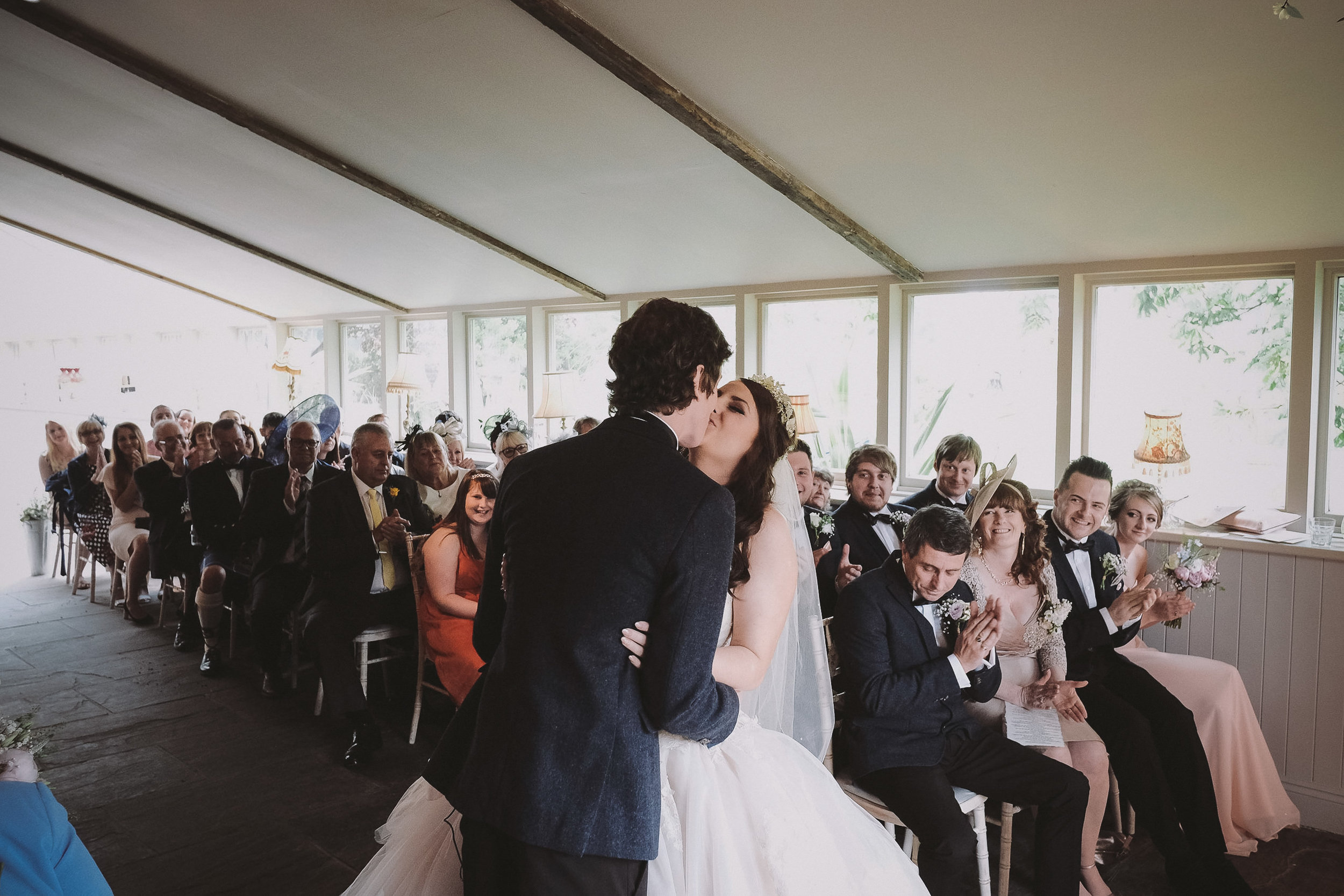 The bride and groom kiss during the wedding ceremony at Newton Hall, Northumberland by Barry Forshaw