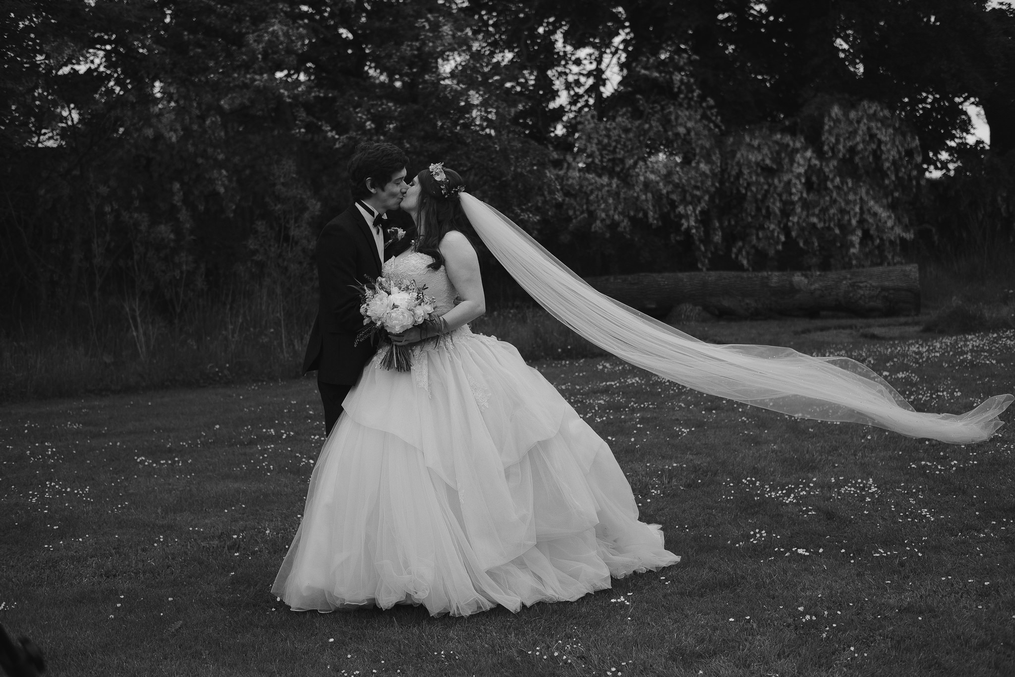 A black and white photo of the bride and groom kissing in the grounds at Newton Hall, Northumberland by Barry Forshaw