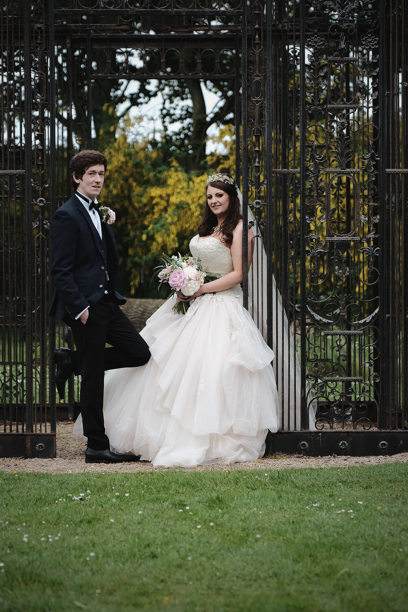 The bride and groom pose in the grounds at Newton Hall, Northumberland by Barry Forshaw