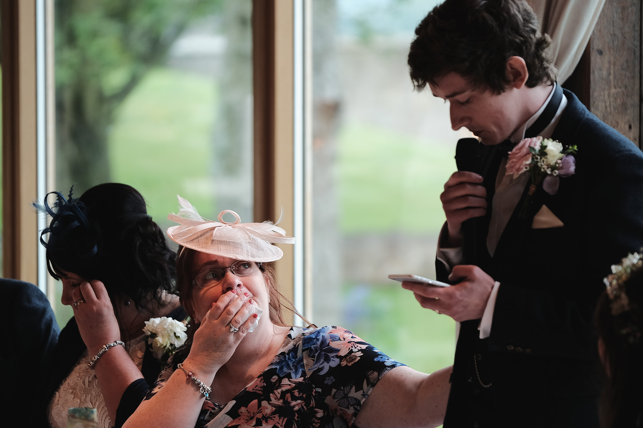 The crying mother of the groom reaches out to the groom as he cries while making his speech at Newton Hall, Northumberland by Barry Forshaw