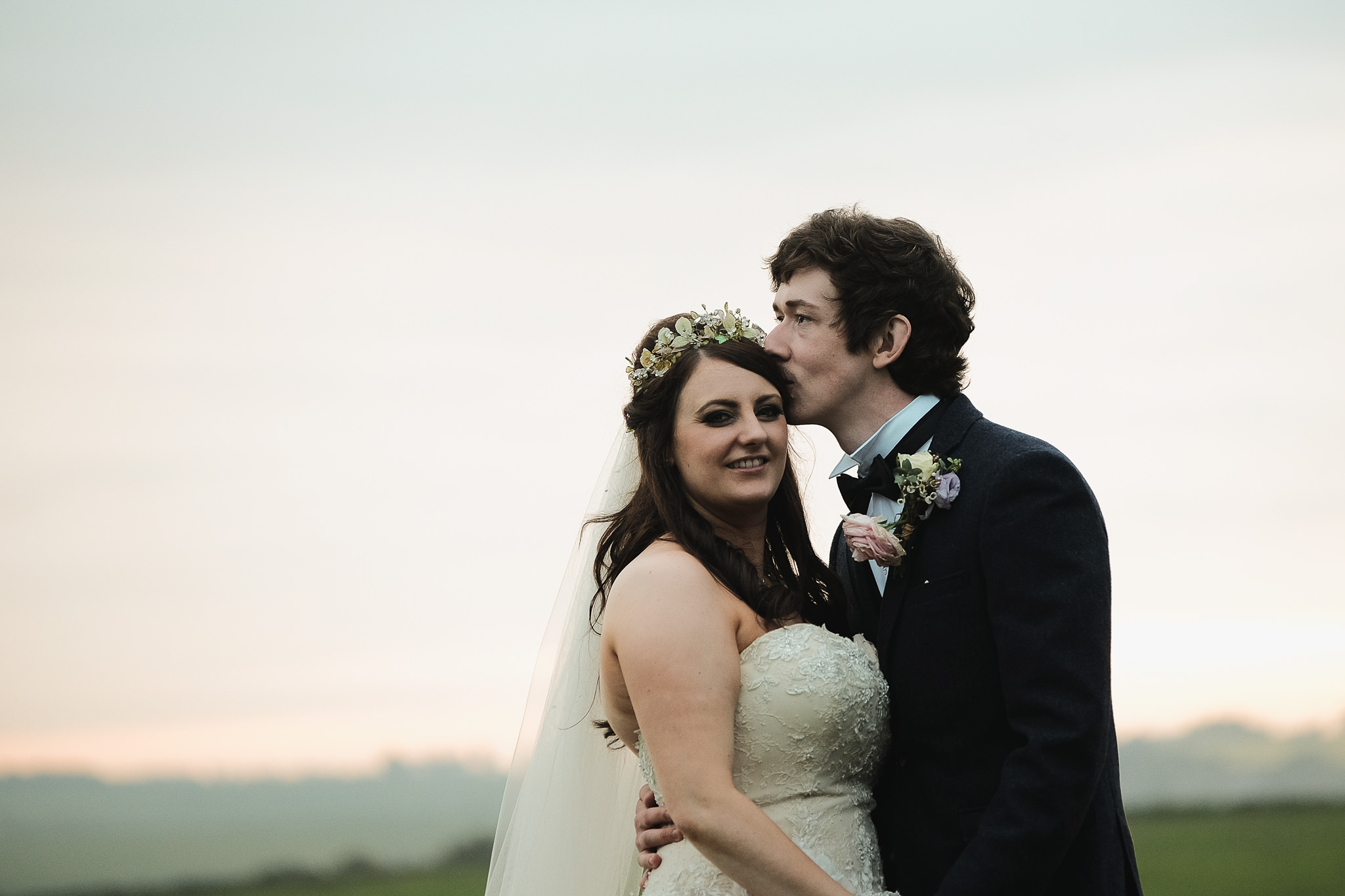 The bride and groom cuddle at Newton Hall, Northumberland by Barry Forshaw