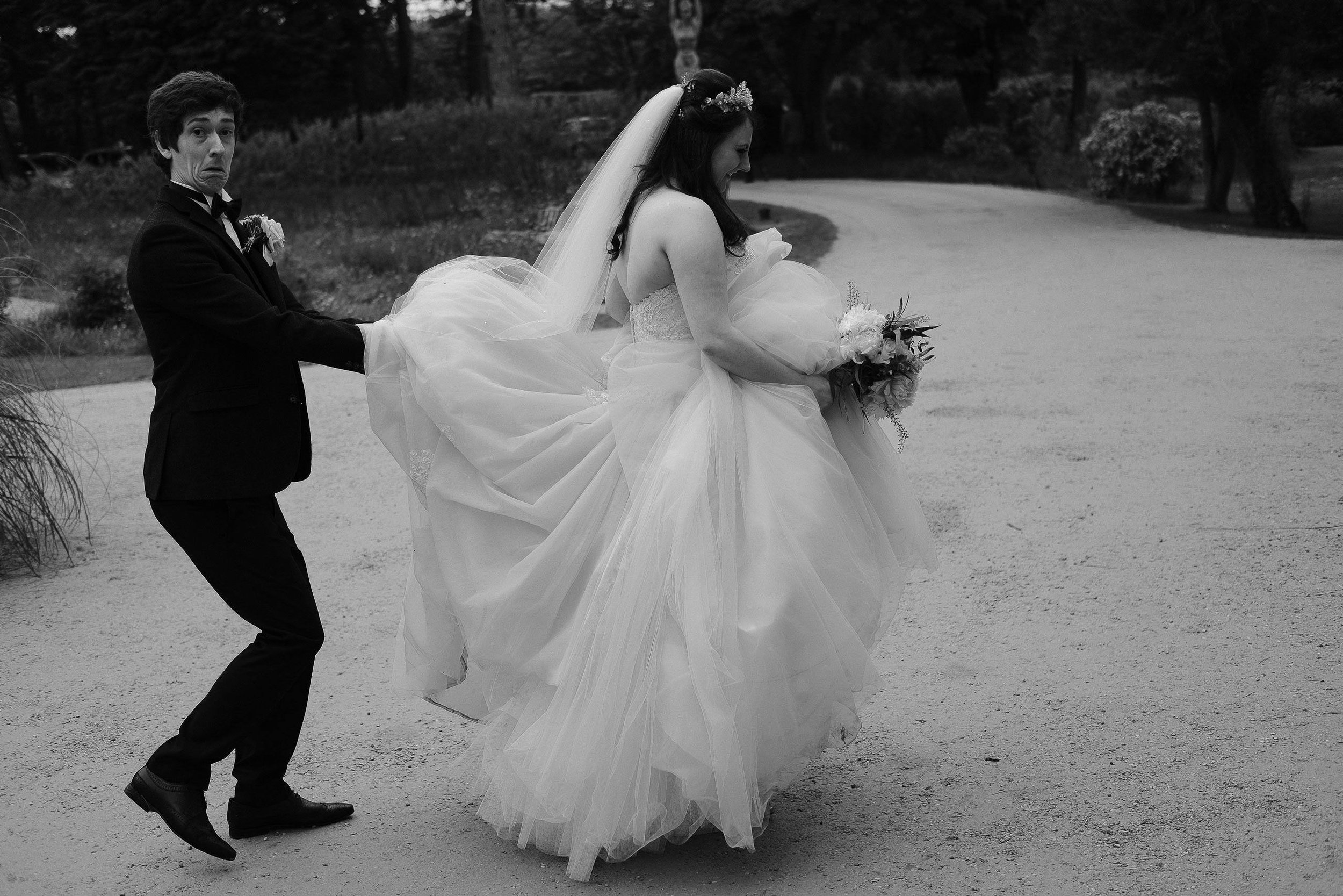 The groom holds up the brides dress and makes a funny face at Newton Hall Northumberland by Barry Forshaw