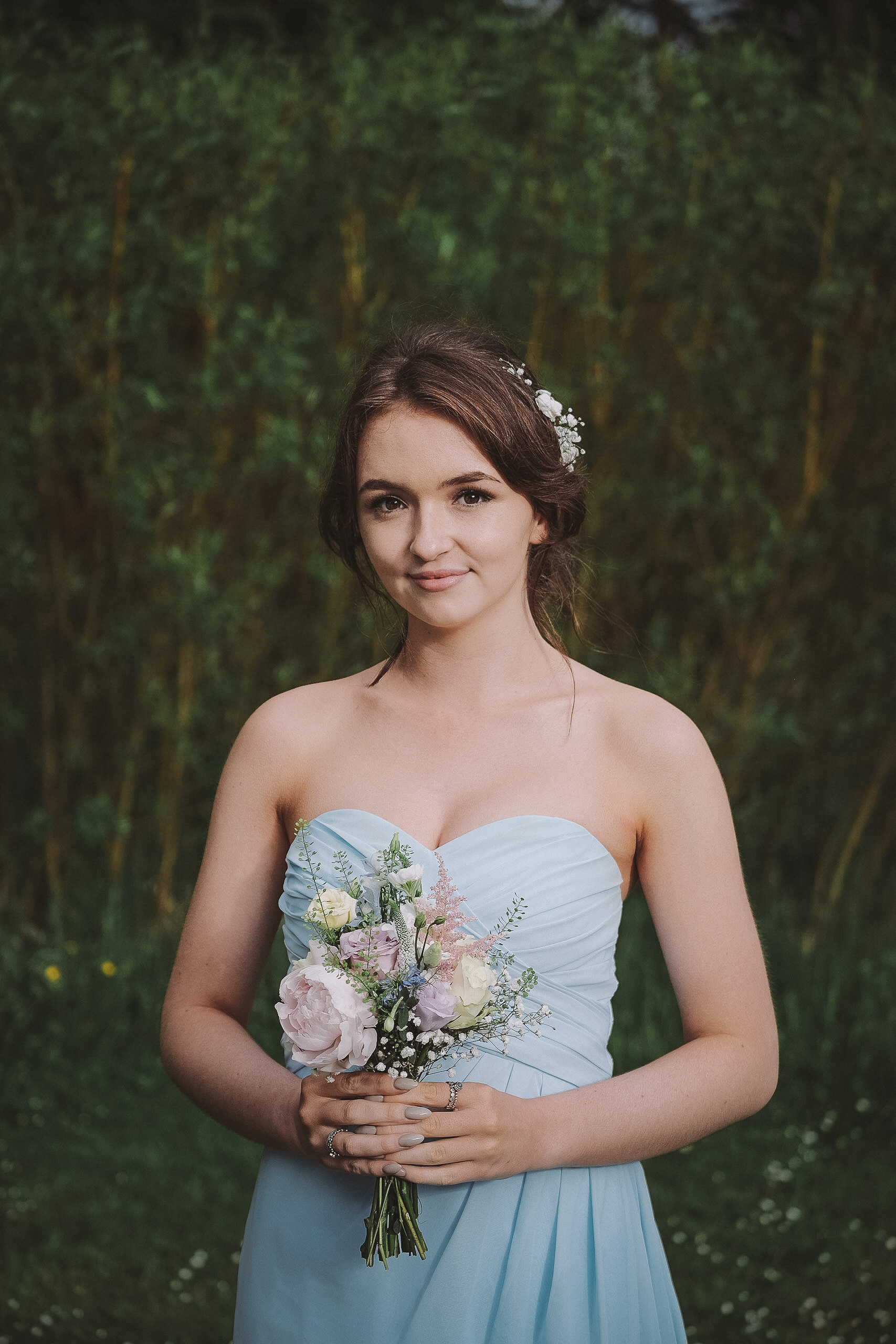 A portrait of a bridesmaid in a pastel blue dress at Newton Hall Northumberland by Barry Forshaw