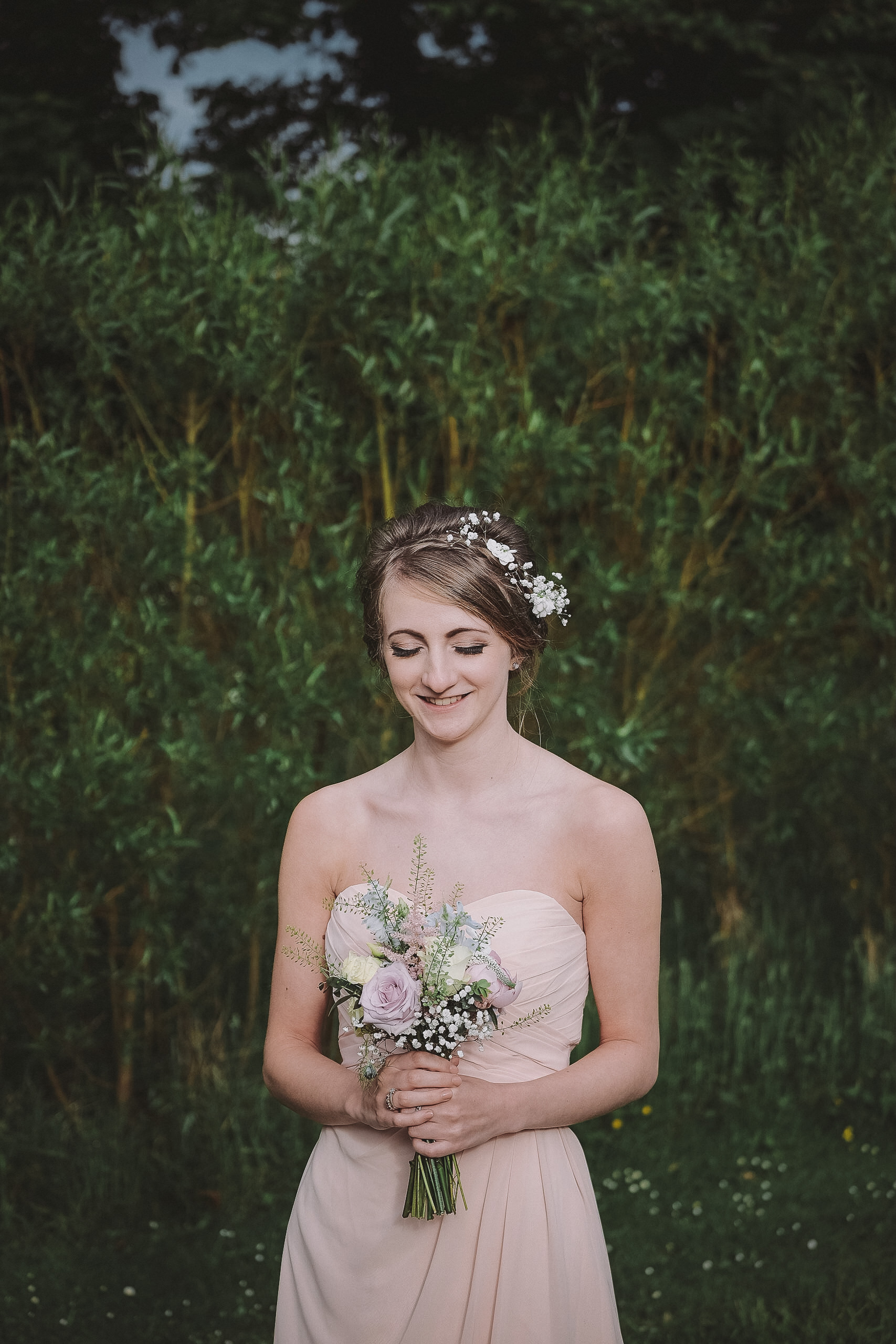 A portrait of a bridesmaid with her eyes closed at Newton Hall Northumberland by Barry Forshaw