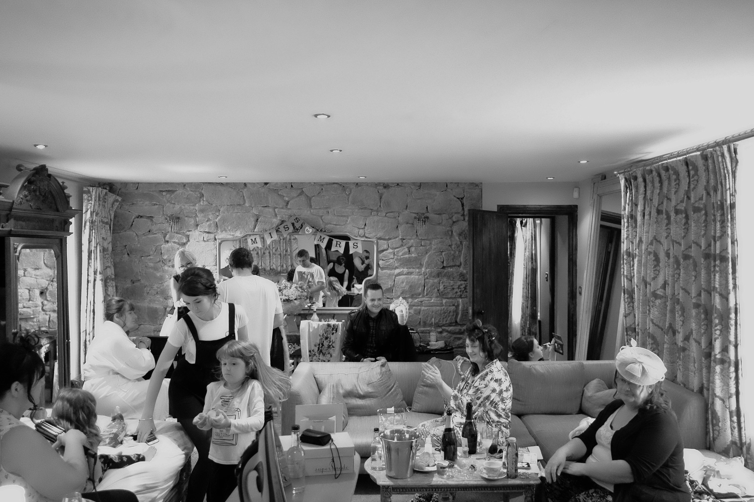 A black and white photo of the Bride, Bridesmaids and Flowergirls getting ready in the same room at Newton Hall, Northumberland by Barry Forshaw