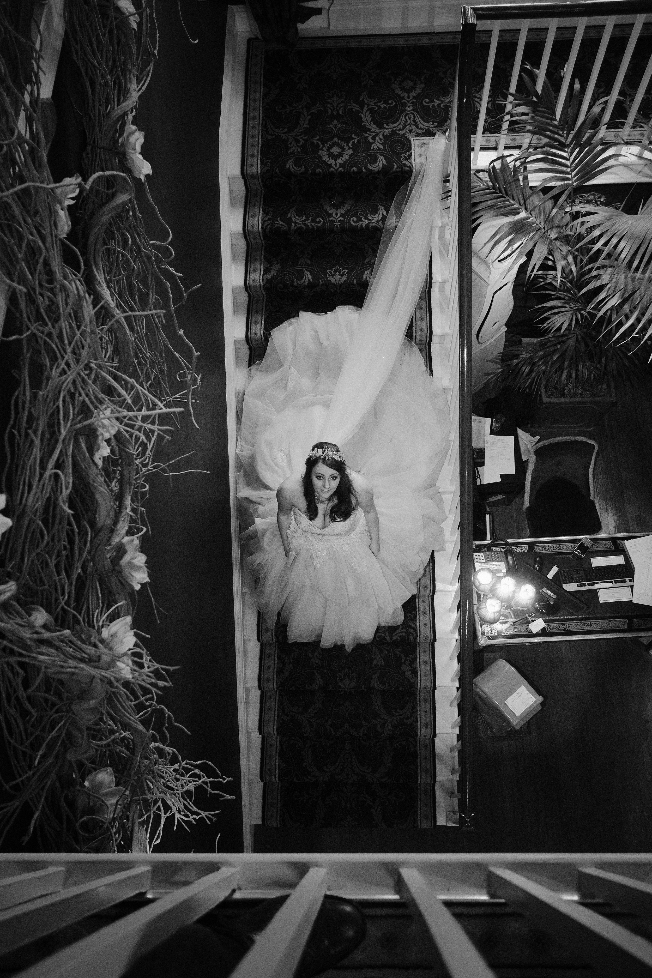 A black and white photo of the bride at the foot of the stairs looking up to the balcony at Newton Hall, Northumberland by Barry Forshaw