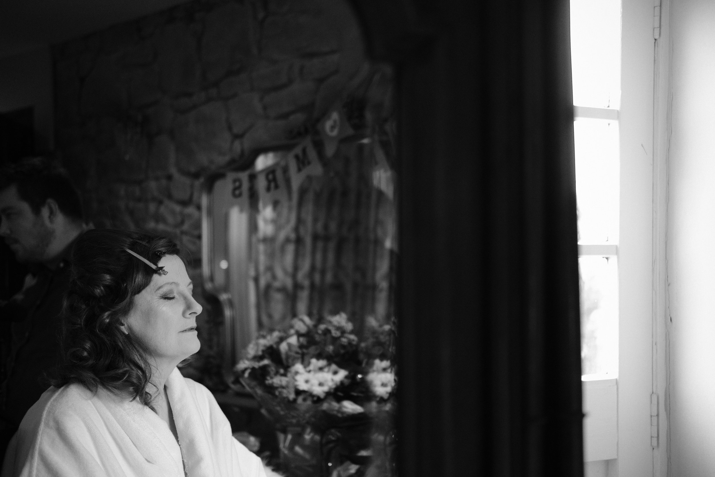 A black and white photograph of the mother of the bride during bridal preparations at Newton Hall, Northumberland by Barry Forshaw