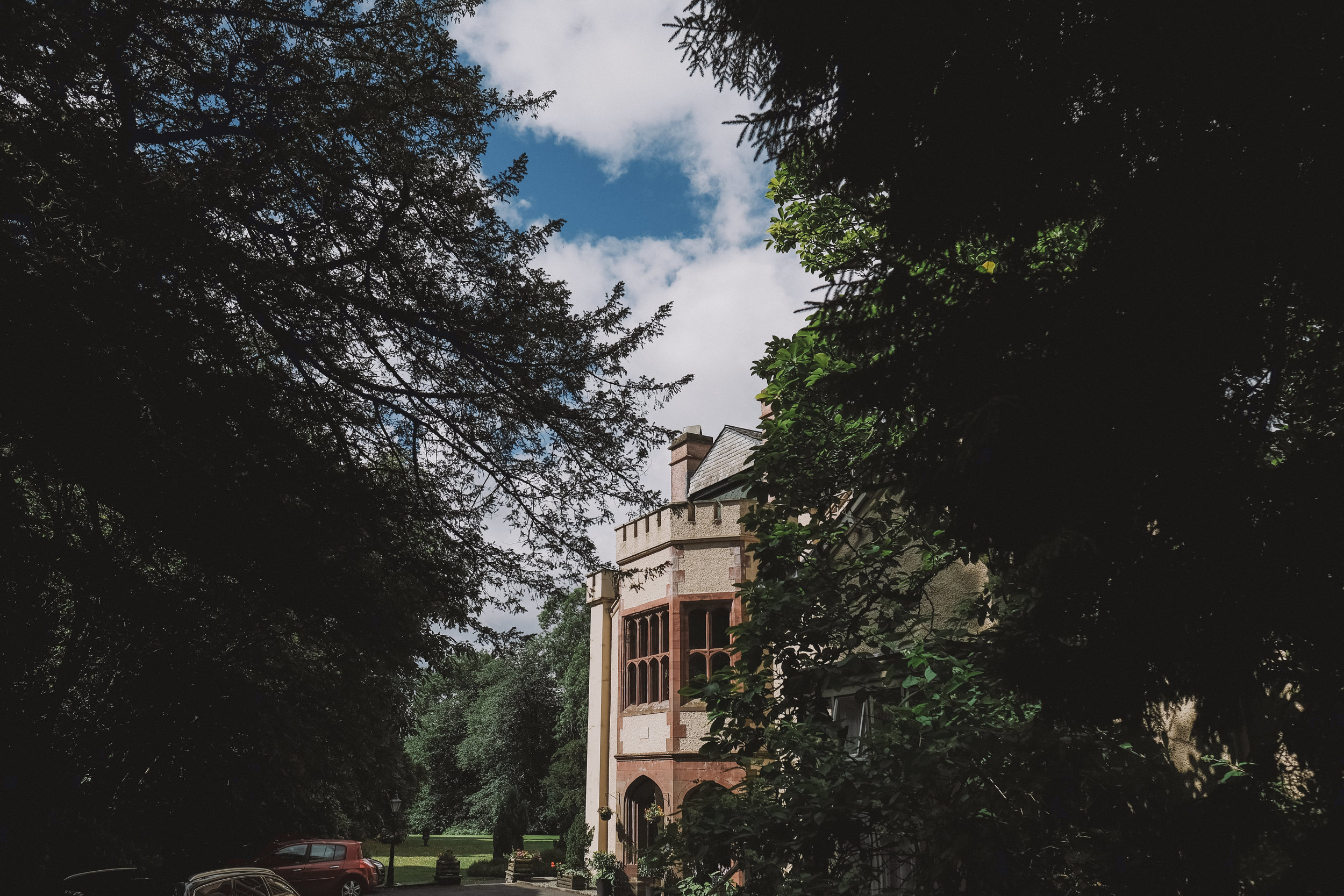 The actual Monk Coniston Hall seen through the trees at Julia and Darren's Lake District wedding by Barry Forshaw