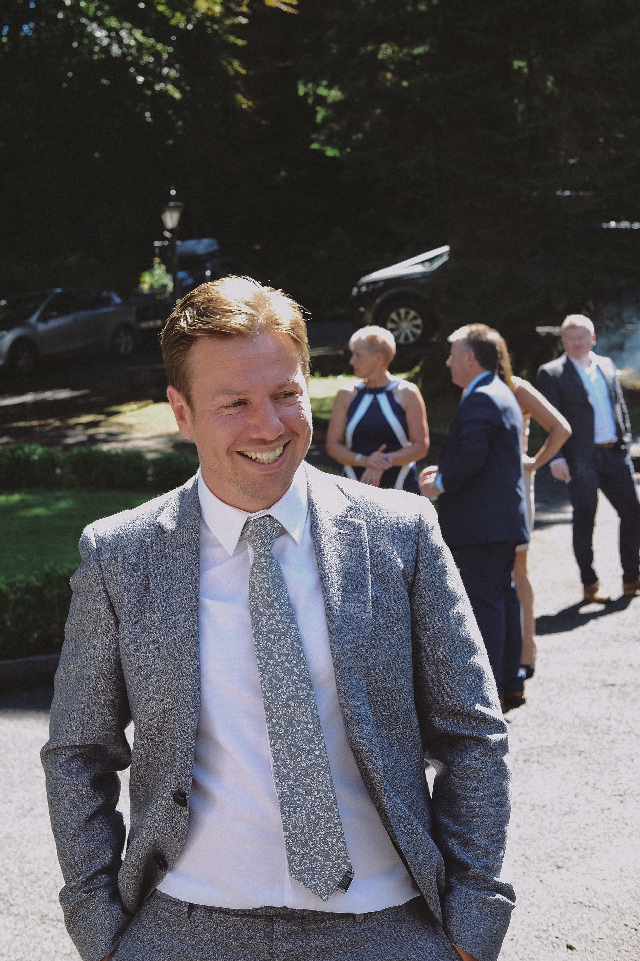 The groom smiles with his guests before his wedding ceremony at Julia and Daren's Lake District wedding by Barry Forshaw