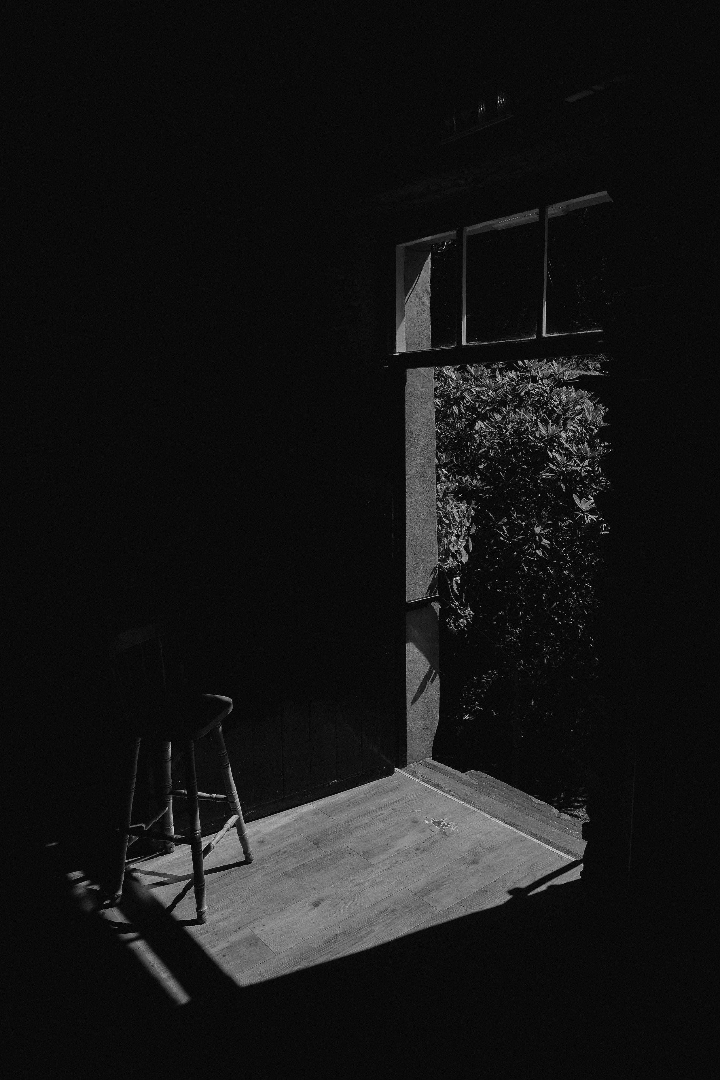 A black and white photo of a chair holding open the door to the ceremony building at Julia and Daren's Lake District wedding by Barry Forshaw
