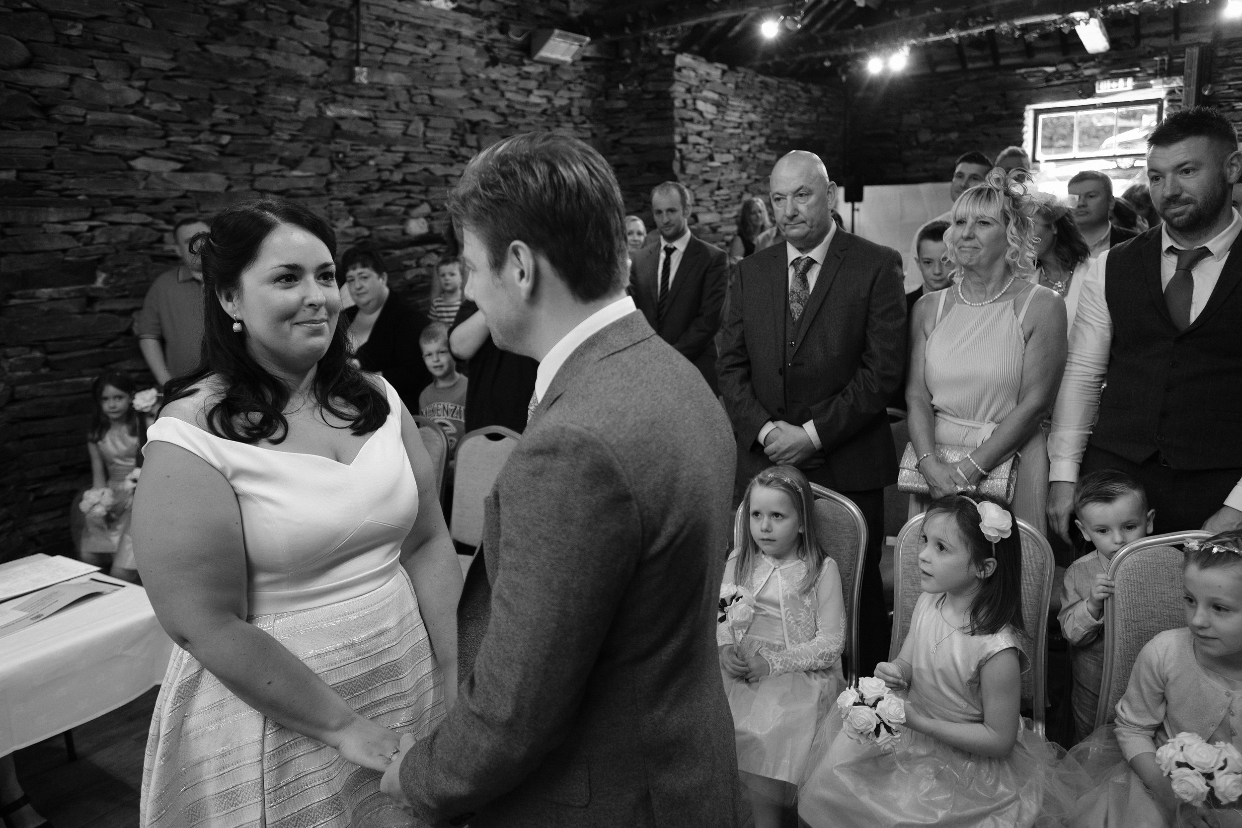 A black and white photo of the bride and groom holding hands during the ceremony at Julia and Darren's Lake District wedding by Barry Forshaw