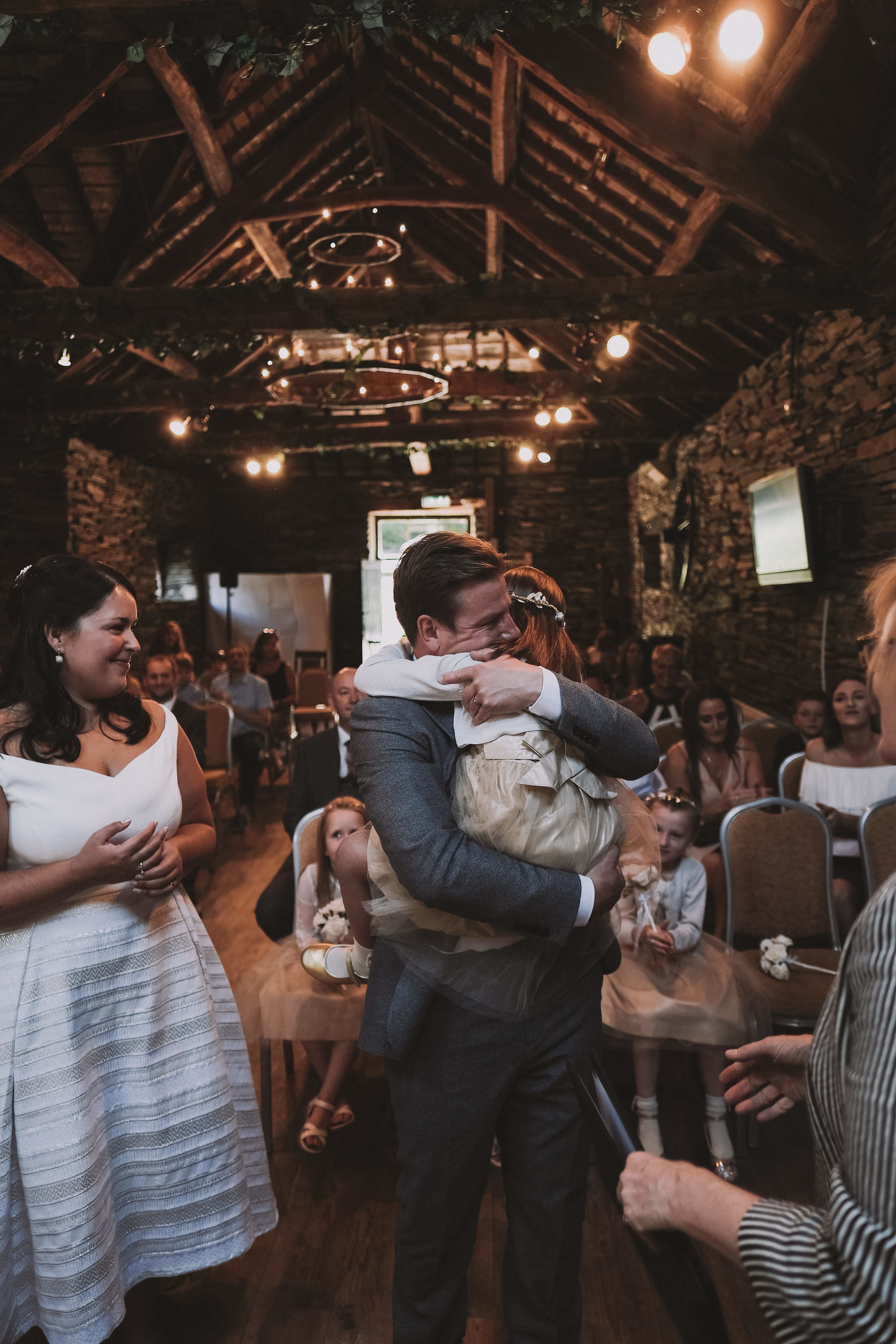 The groom hugs his daughter during the wedding ceremony at Julia and Darren's Lake District wedding by Barry Forshaw