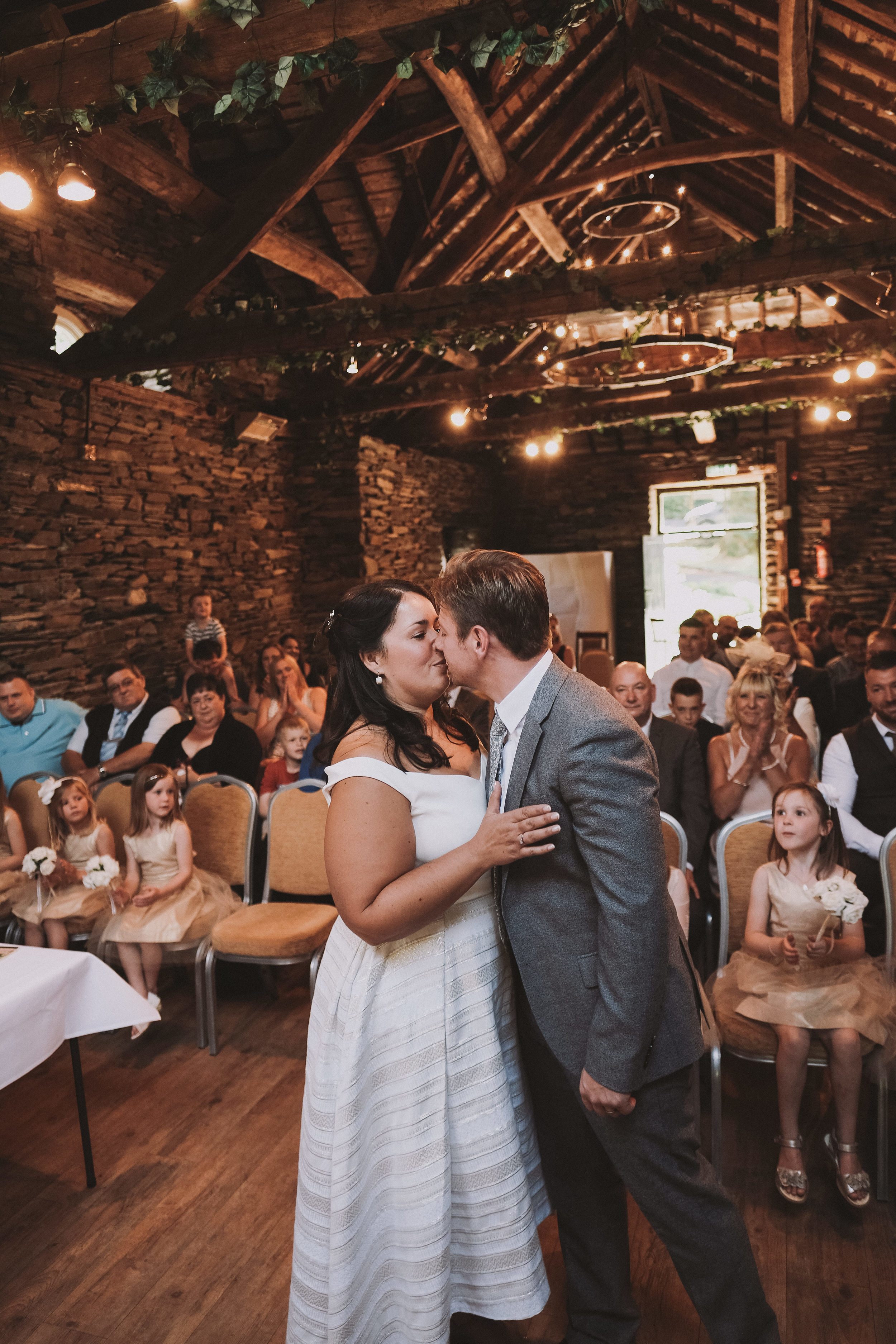 The bride and groom kiss during the ceremony at Julia and Darren's Lake District wedding by Barry Forshaw