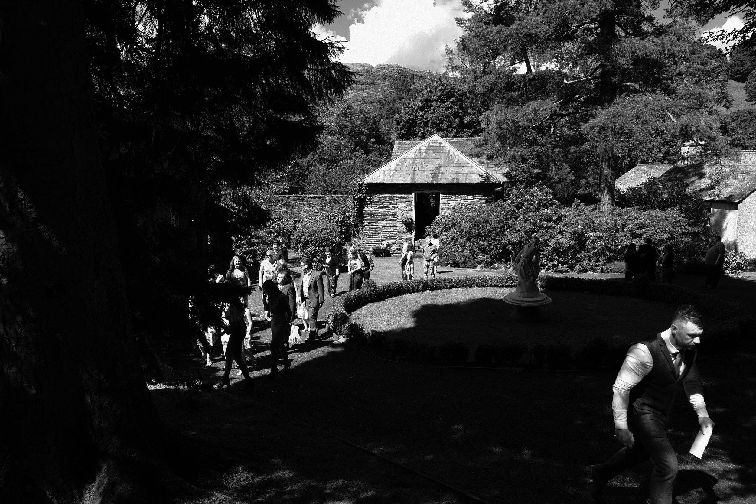 A black and white photo of the guests leaving the wedding ceremony at Julia and Darren's Lake District wedding by Barry Forshaw