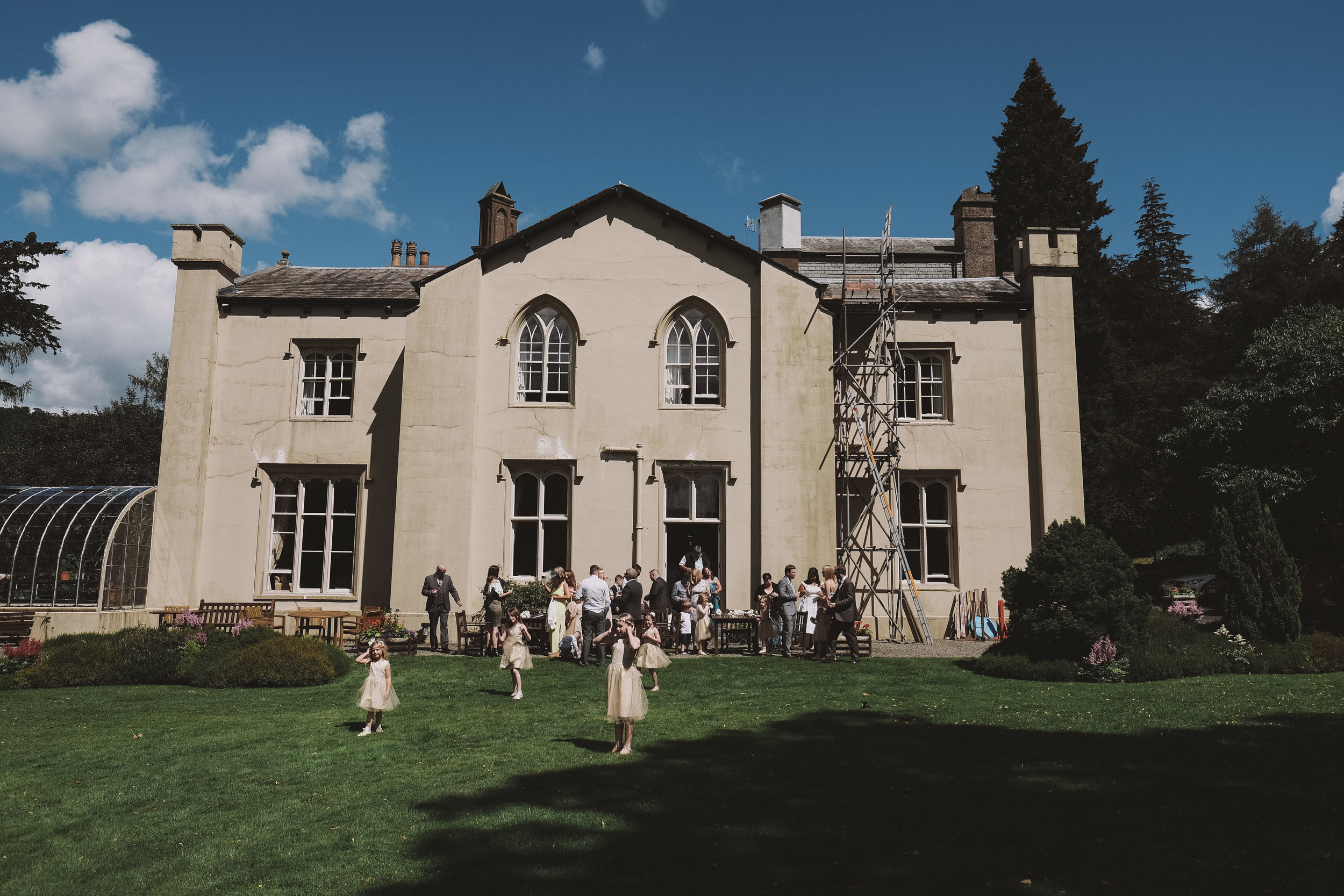 Children play on the grass outside Monk Coniston Hall at Julia and Darren's Lake District wedding by Barry Forshaw