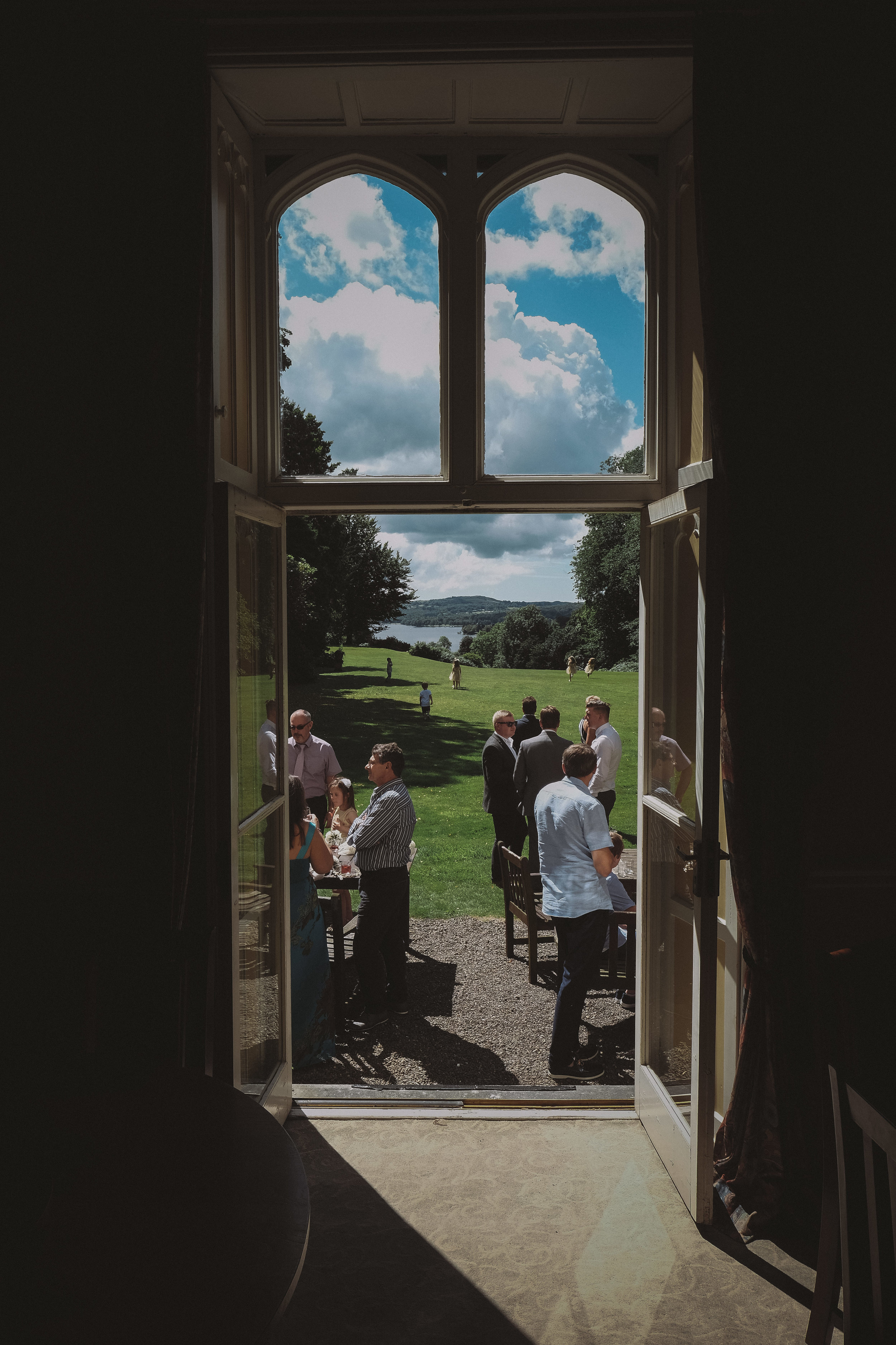 Guests glimpsed through the door of Monk Coniston Hall with Coniston Water in the background at Julia and Darren's Lake District wedding by Barry Forshaw