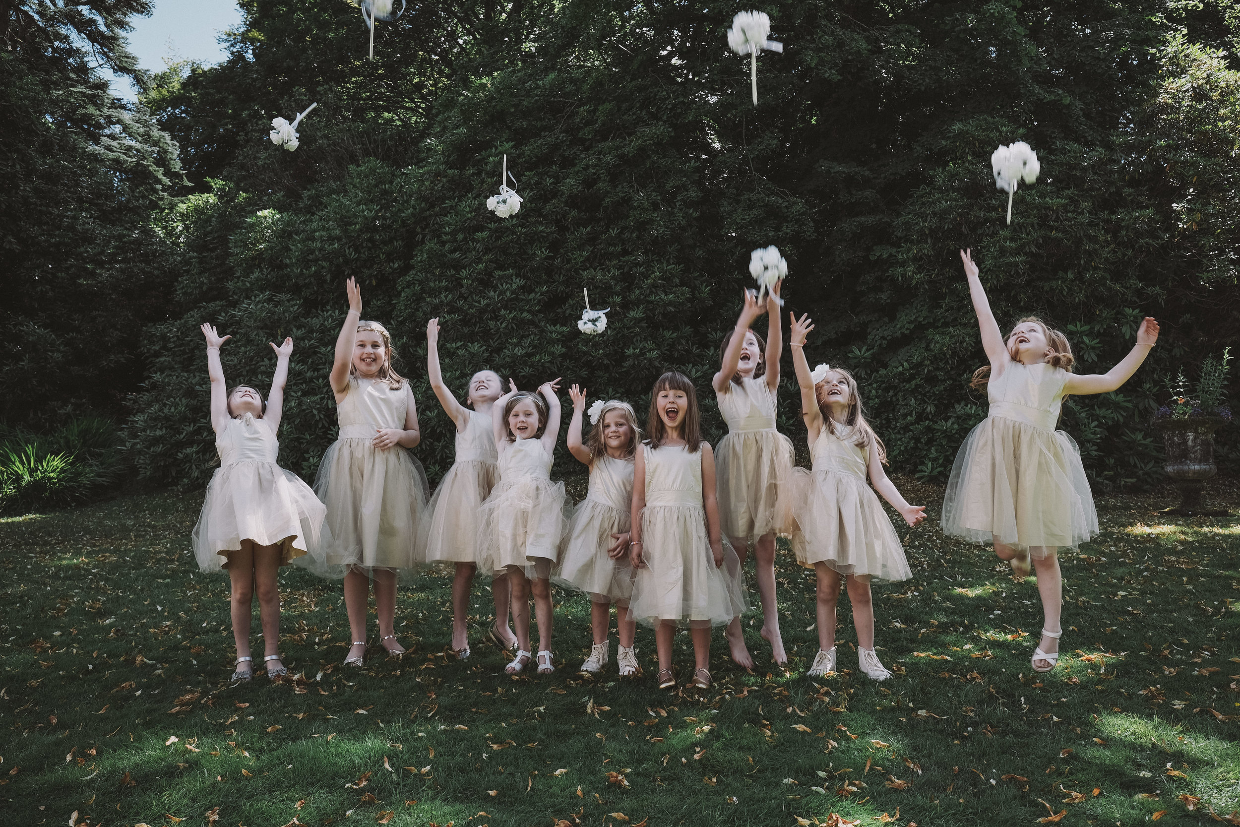 Flower girls toss their flowers in the air at Julia and Darren's Lake District wedding by Barry Forshaw