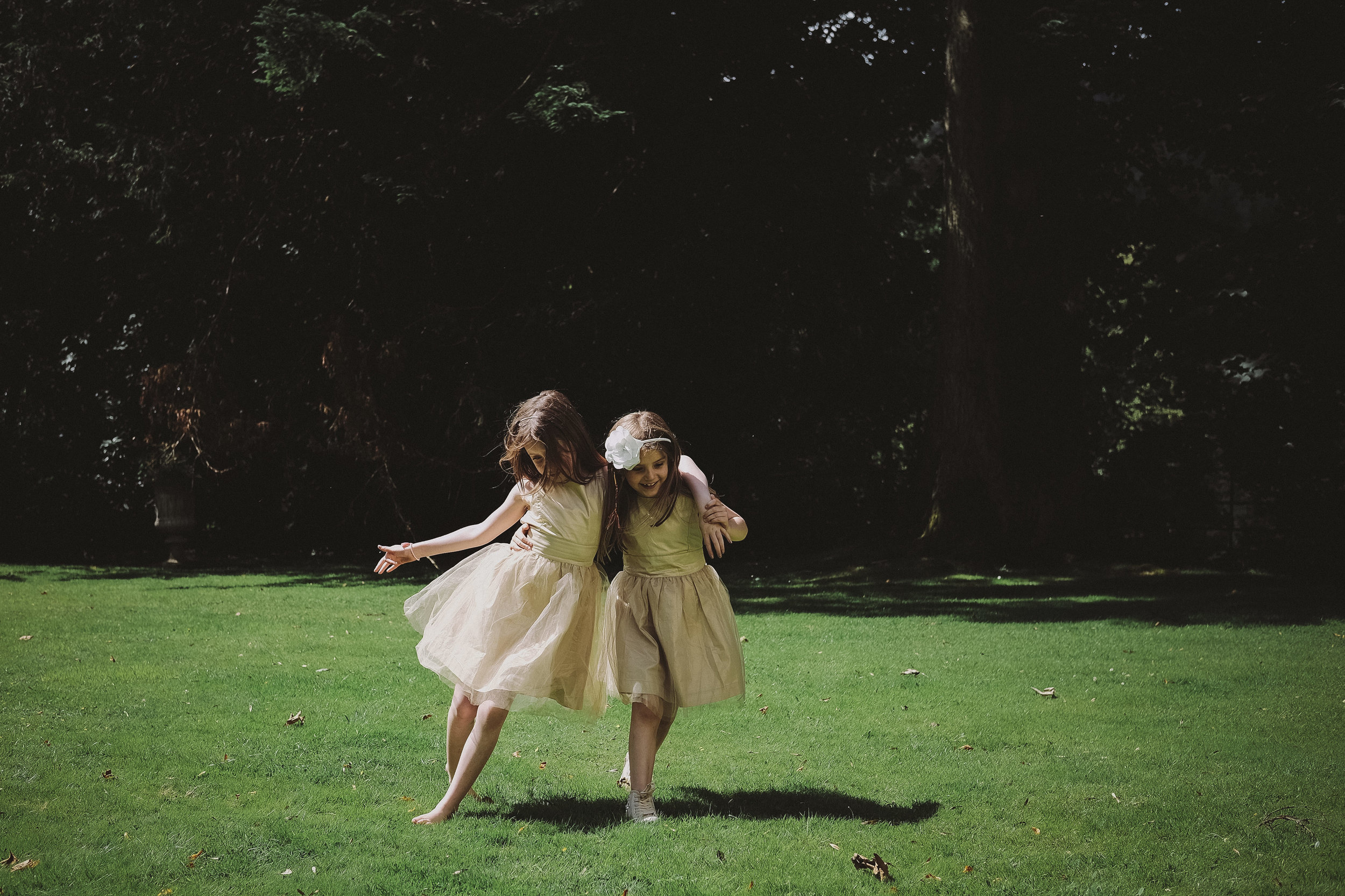 Two flower girls hold each other up on the grass at Julia and Darren's Lake District wedding by Barry Forshaw