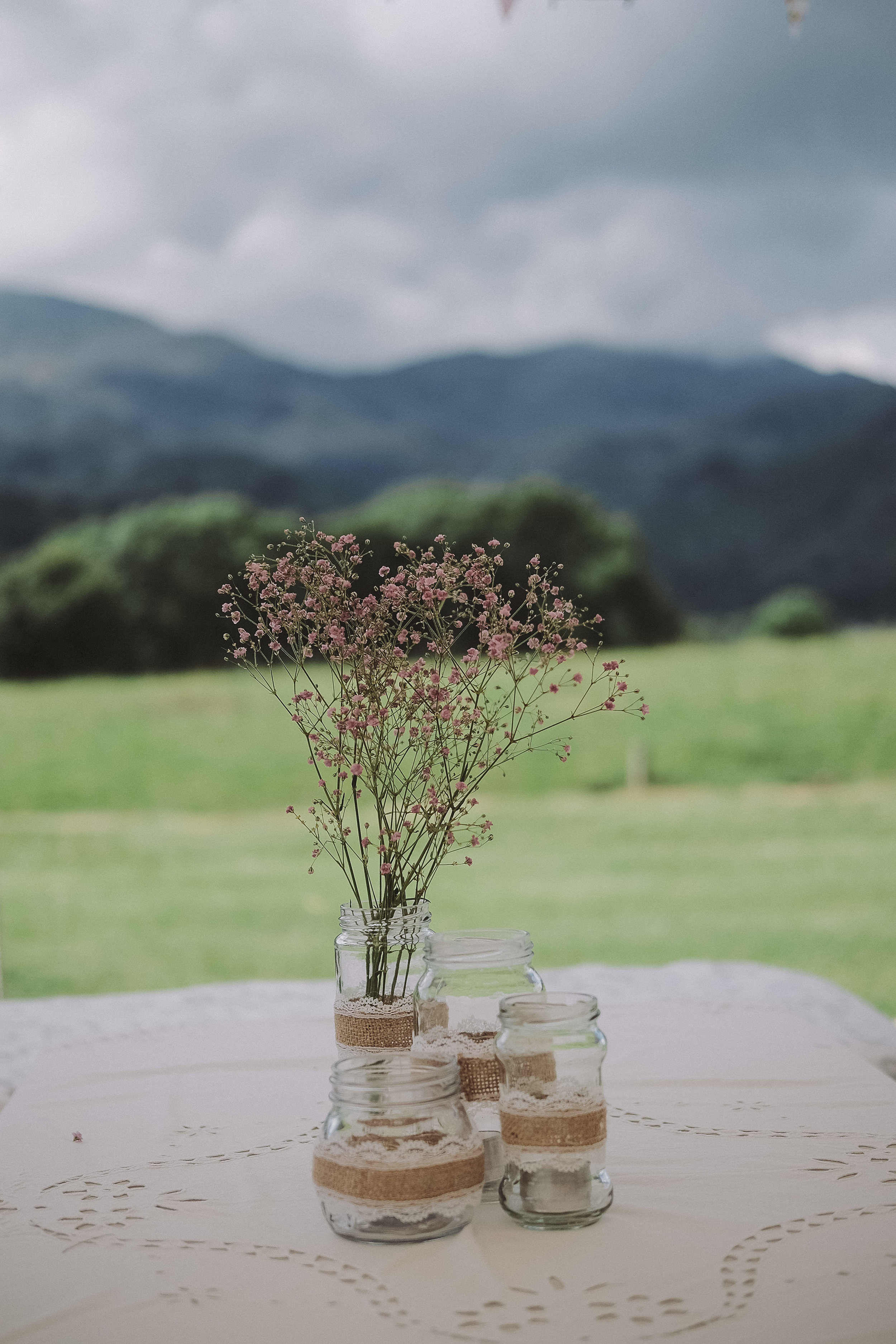 A flower centrepiece with the hills of the Lake District in the background at Julia and Darren's Lake District wedding by Barry Forshaw