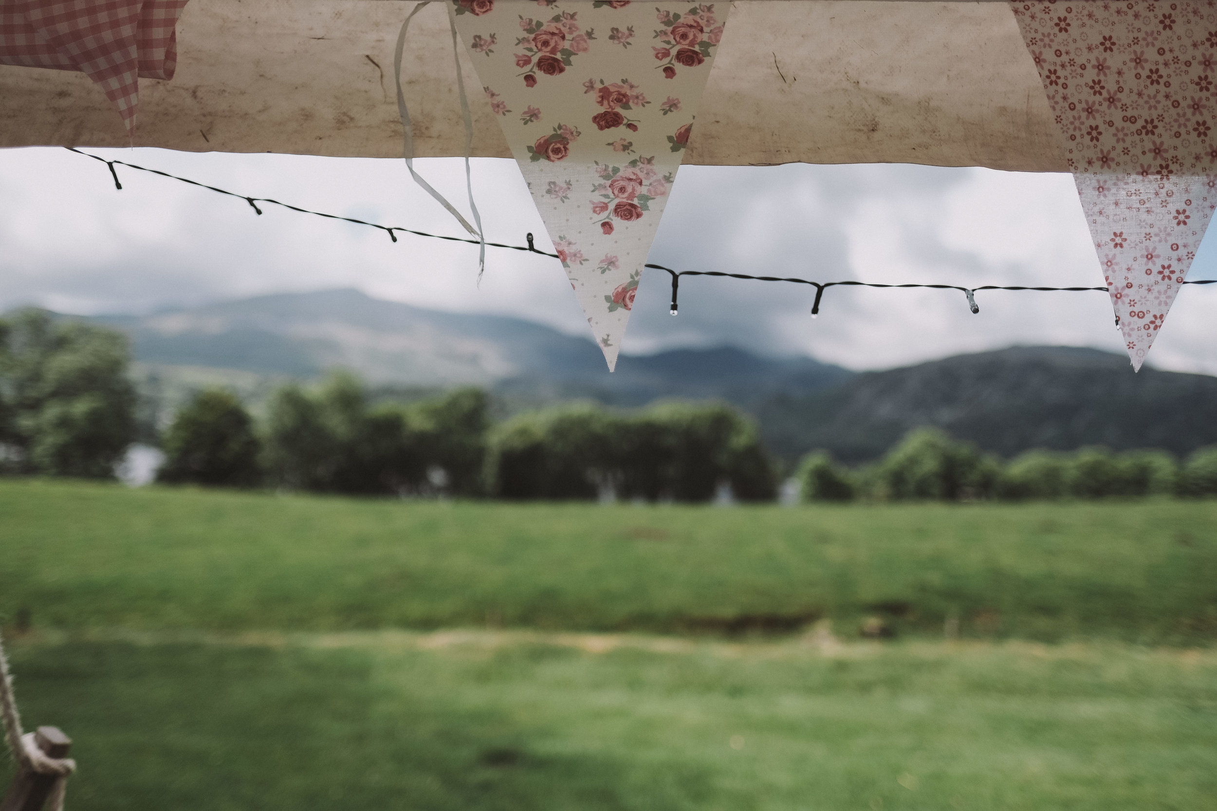 Bunting in the marquee with the hills over Coniston water out of focus in the background at Julia and Darren's Lake District wedding by Barry Forshaw