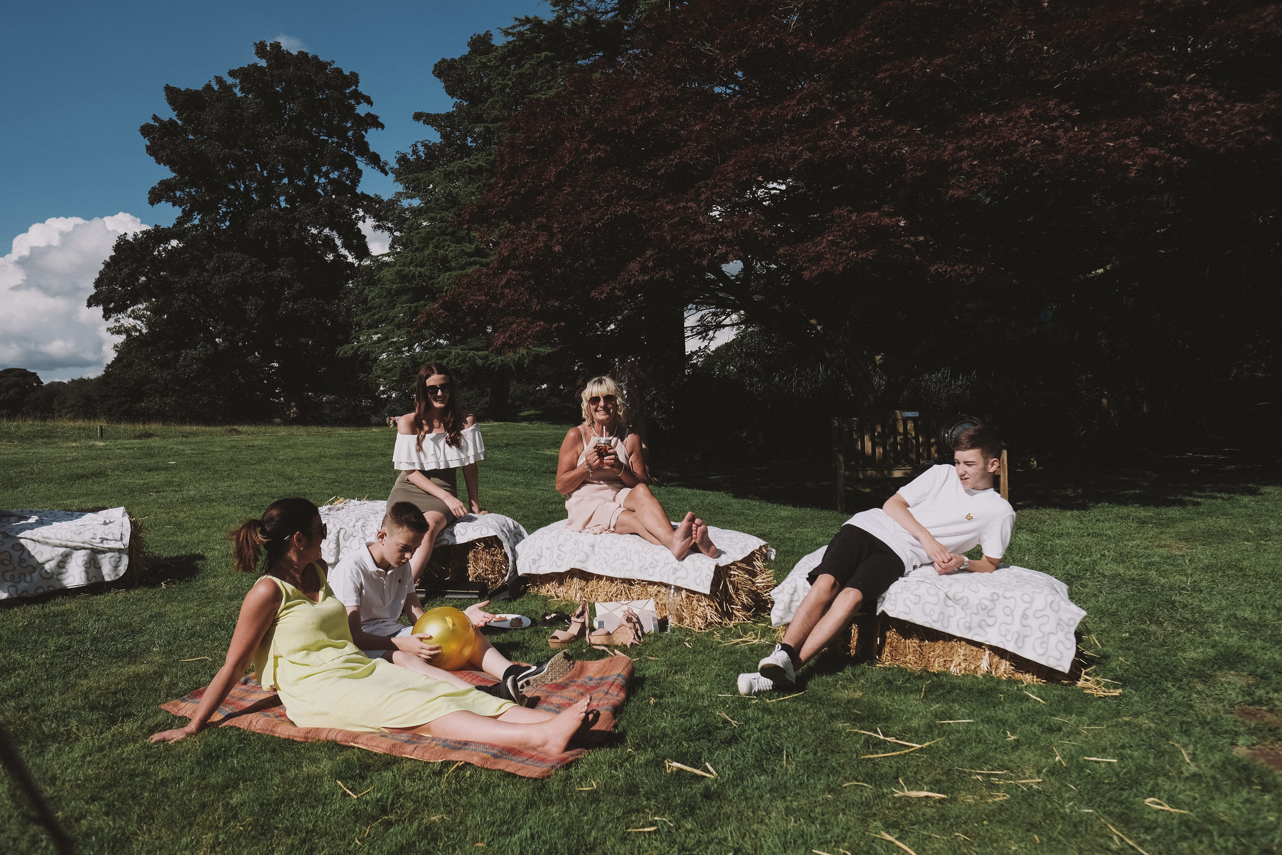 Wedding guests sit on hay bales at Julia and Darren's Lake District wedding by Barry Forshaw