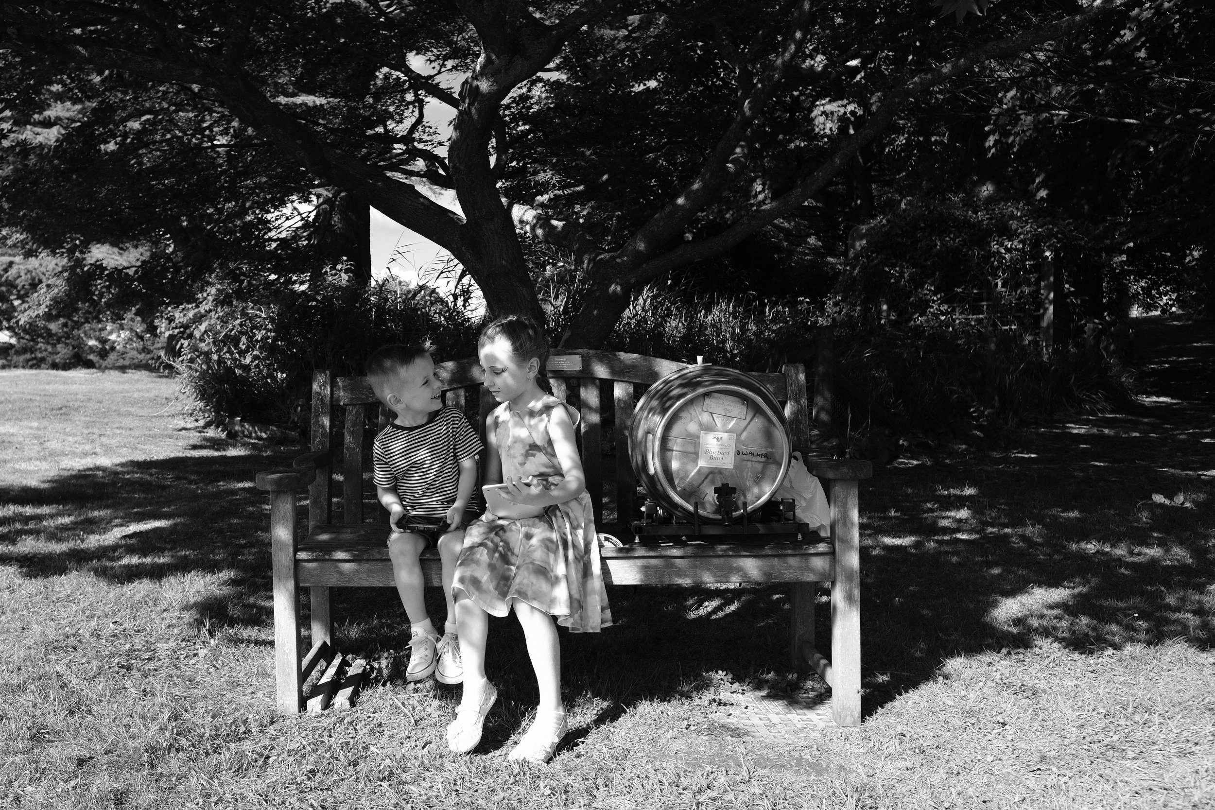 A black and white photo of two children sitting on a bench with a beer barrel at Julia and Darren's Lake District wedding by Barry Forshaw