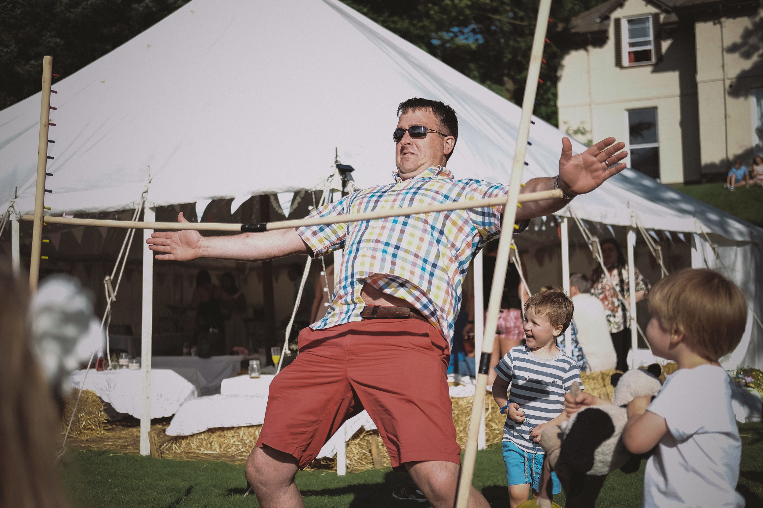 A wedding guest limbo dances at Julia and Darren's Lake District wedding by Barry Forshaw