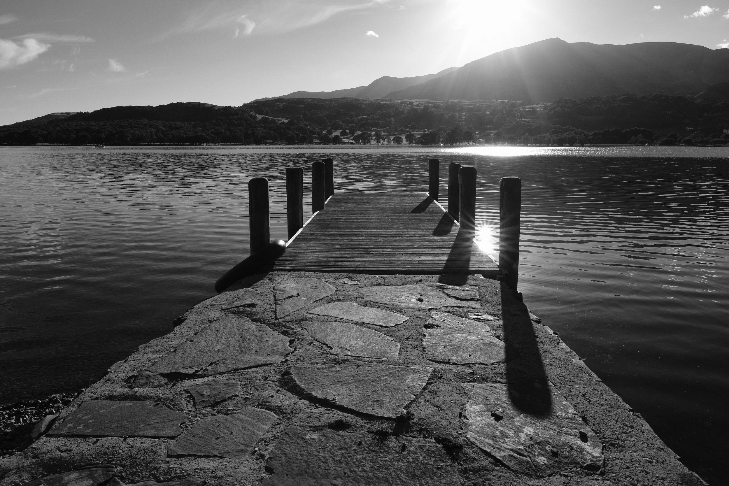 A black and white photo of a jetty on Coniston Water at Julia and Darren's Lake District wedding by Barry Forshaw