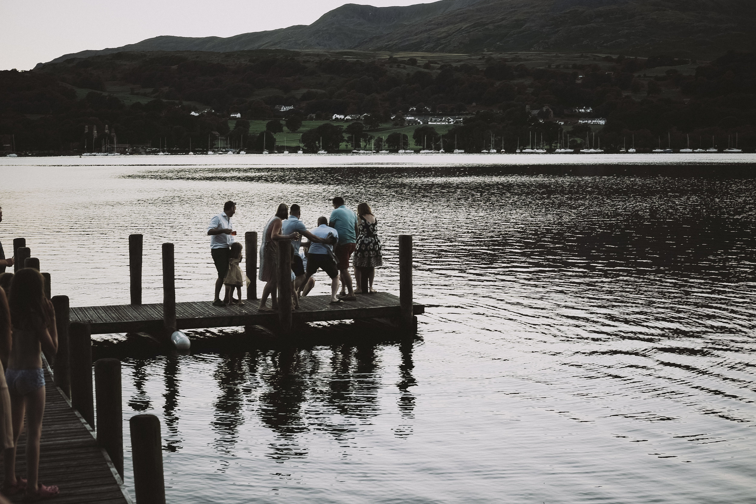 The wedding guests throw the groom into Coniston water at Julia and Darren's Lake District wedding by Barry Forshaw