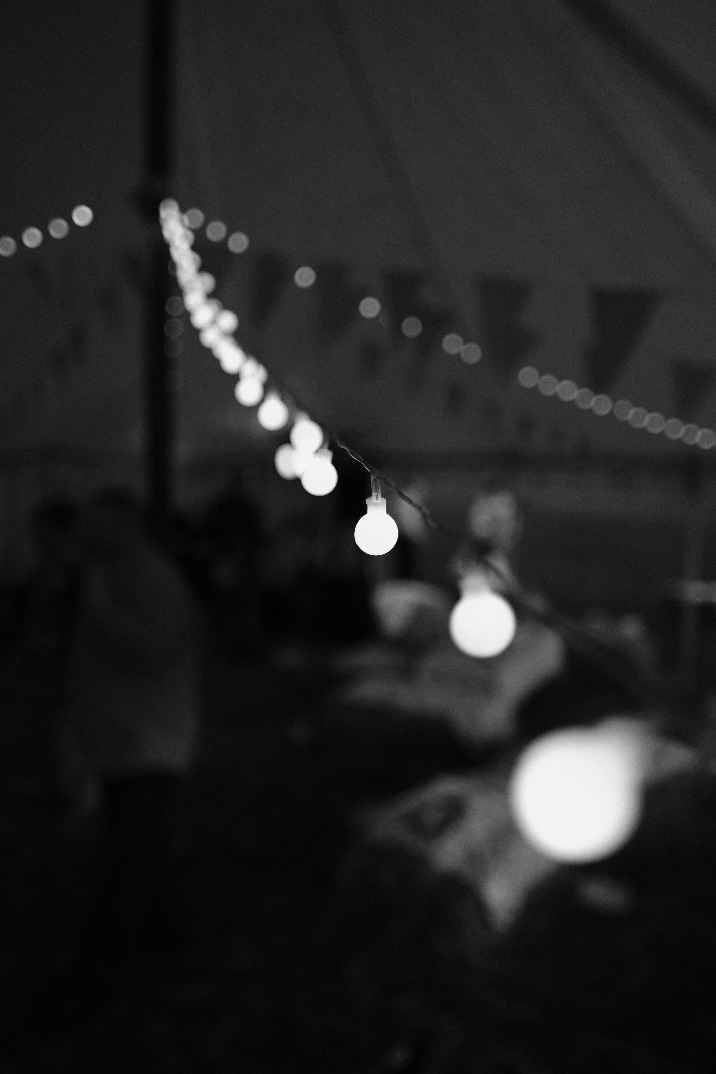 A black and white photo of the lights strung up in the marquee at Julia and Darren's Lake District wedding by Barry Forshaw