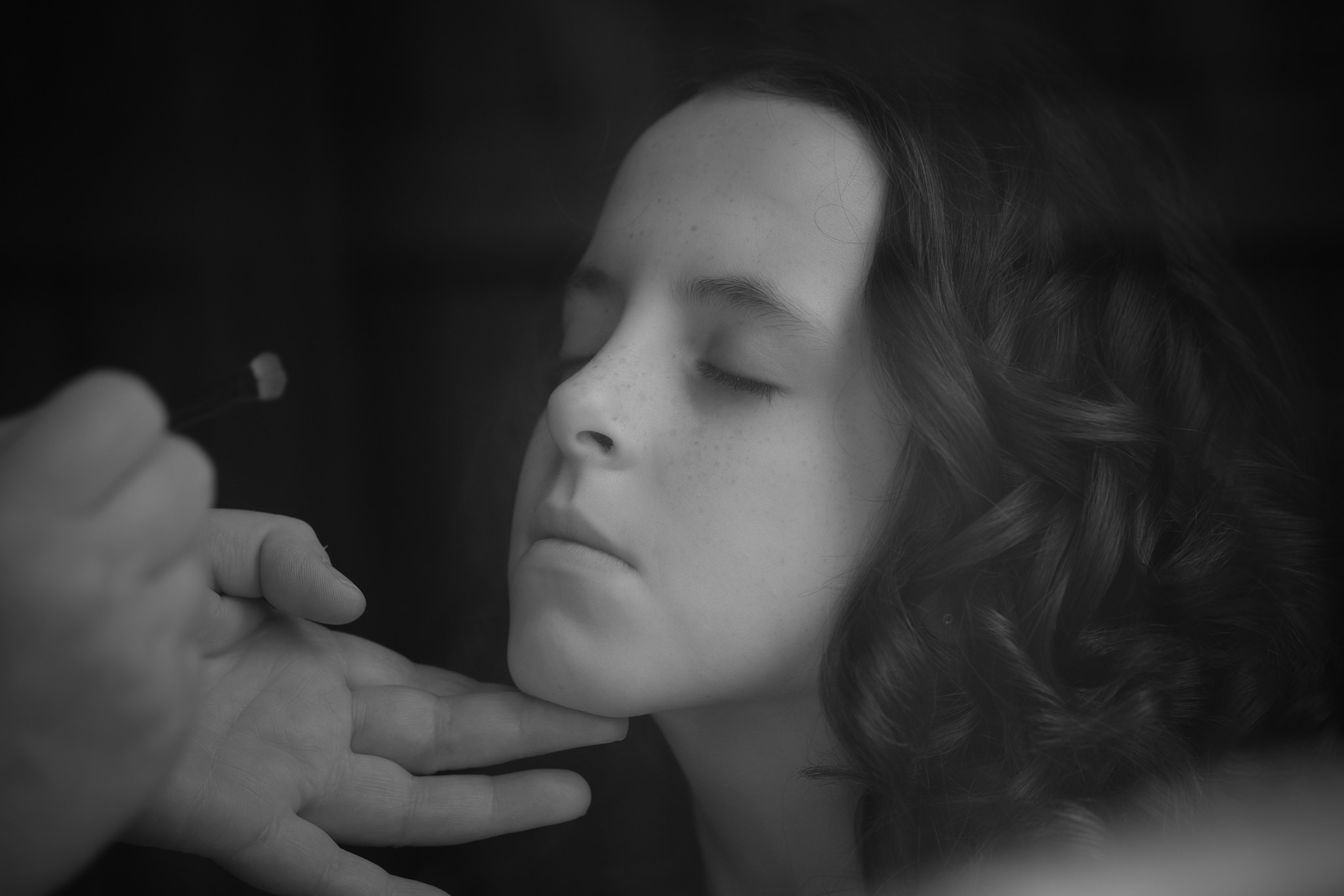 Black and white portrait of flower girl having her makeup applied