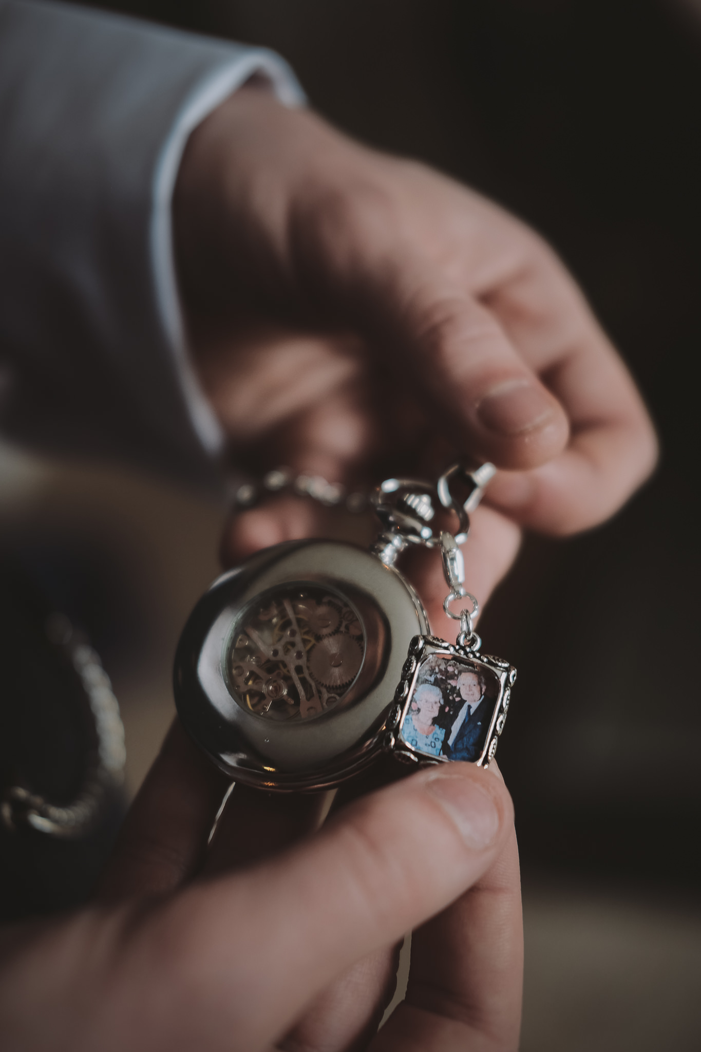 Groom looks at his pocket watch which contains a photo of his grandparents at Newton Hall Northumberland