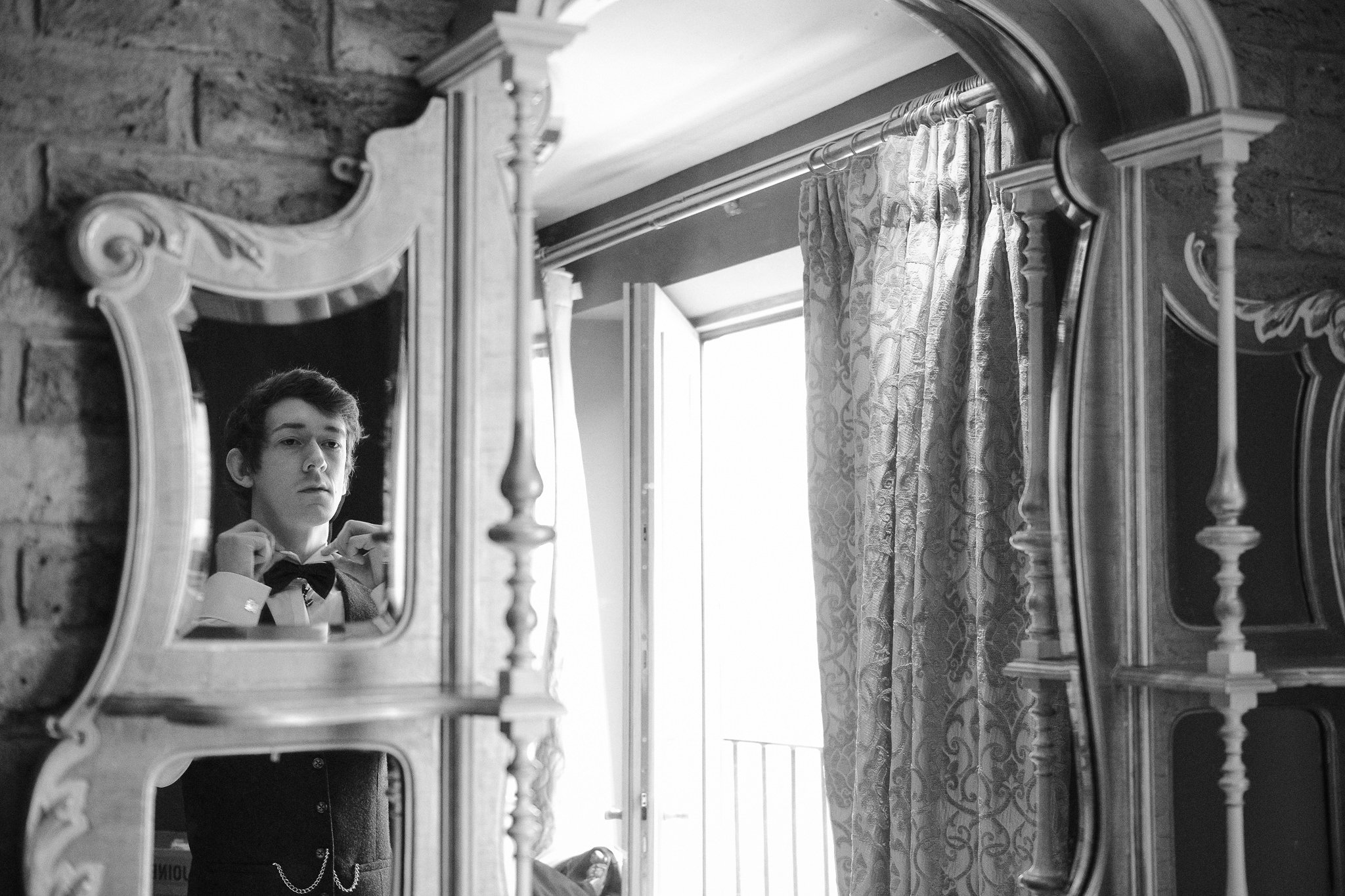 Groom adjusts his bow tie in the mirror in a black and white photo taken at Newton Hall