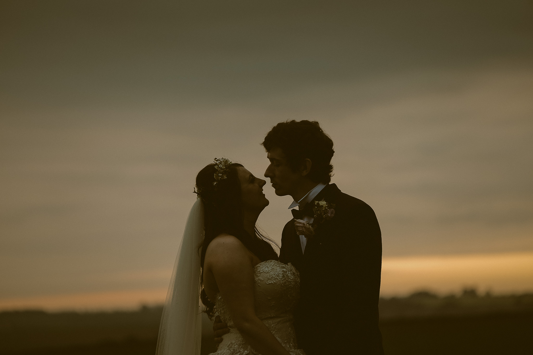 Bride and groom look into each others eyes with a golden sunset behind