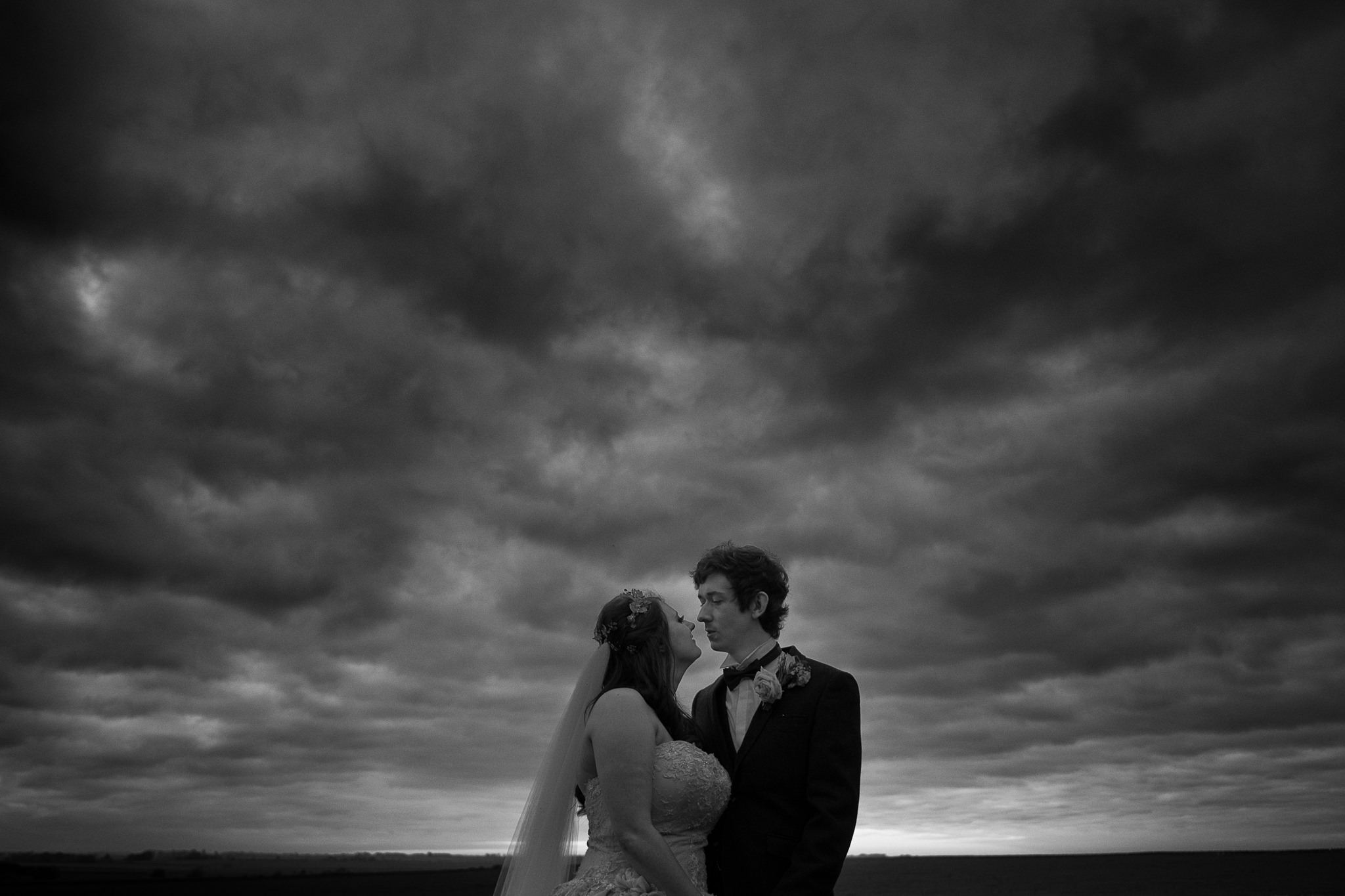black and white photo of a bride and groom underneath a cloudy dramatic sky