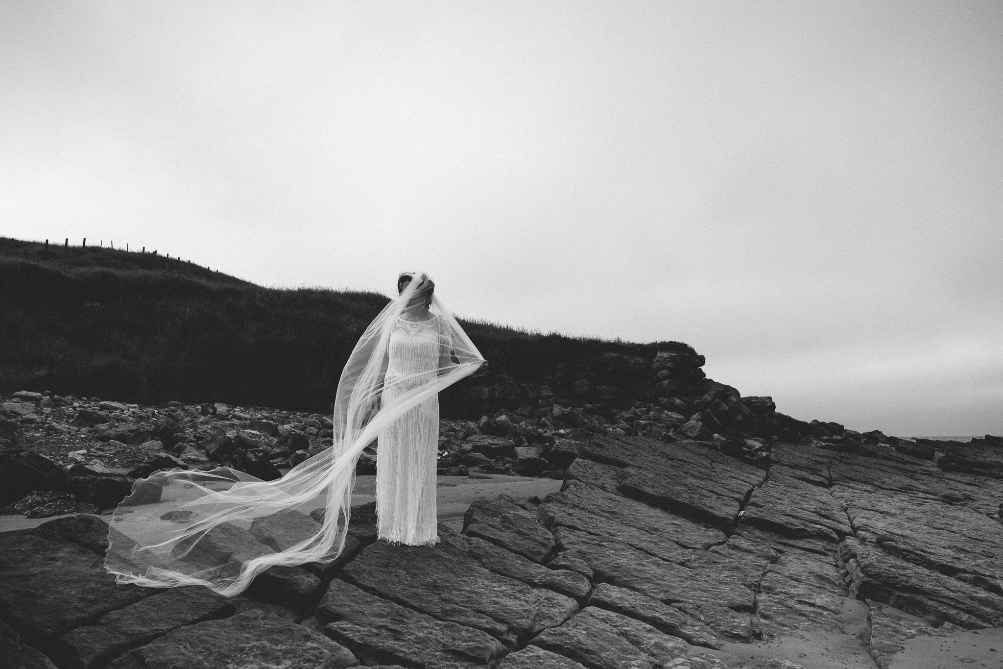 A black and white photo of a bride standing on rocks with her veil blowing in the wind